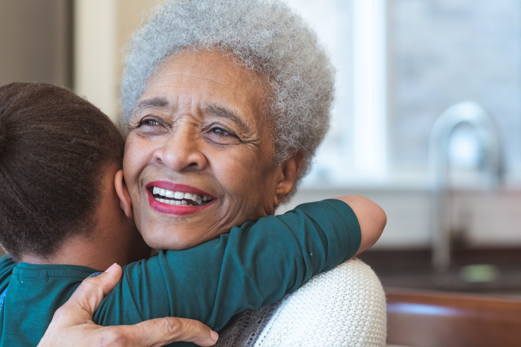 Granddaughter and Grandmother embrace at Forest Creek Memory Care in Overland Park, Kansas