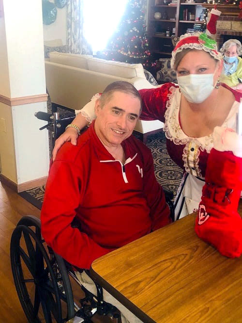 Resident receiving a stocking from a caretaker at Ashbrook Village in Duncan, Oklahoma