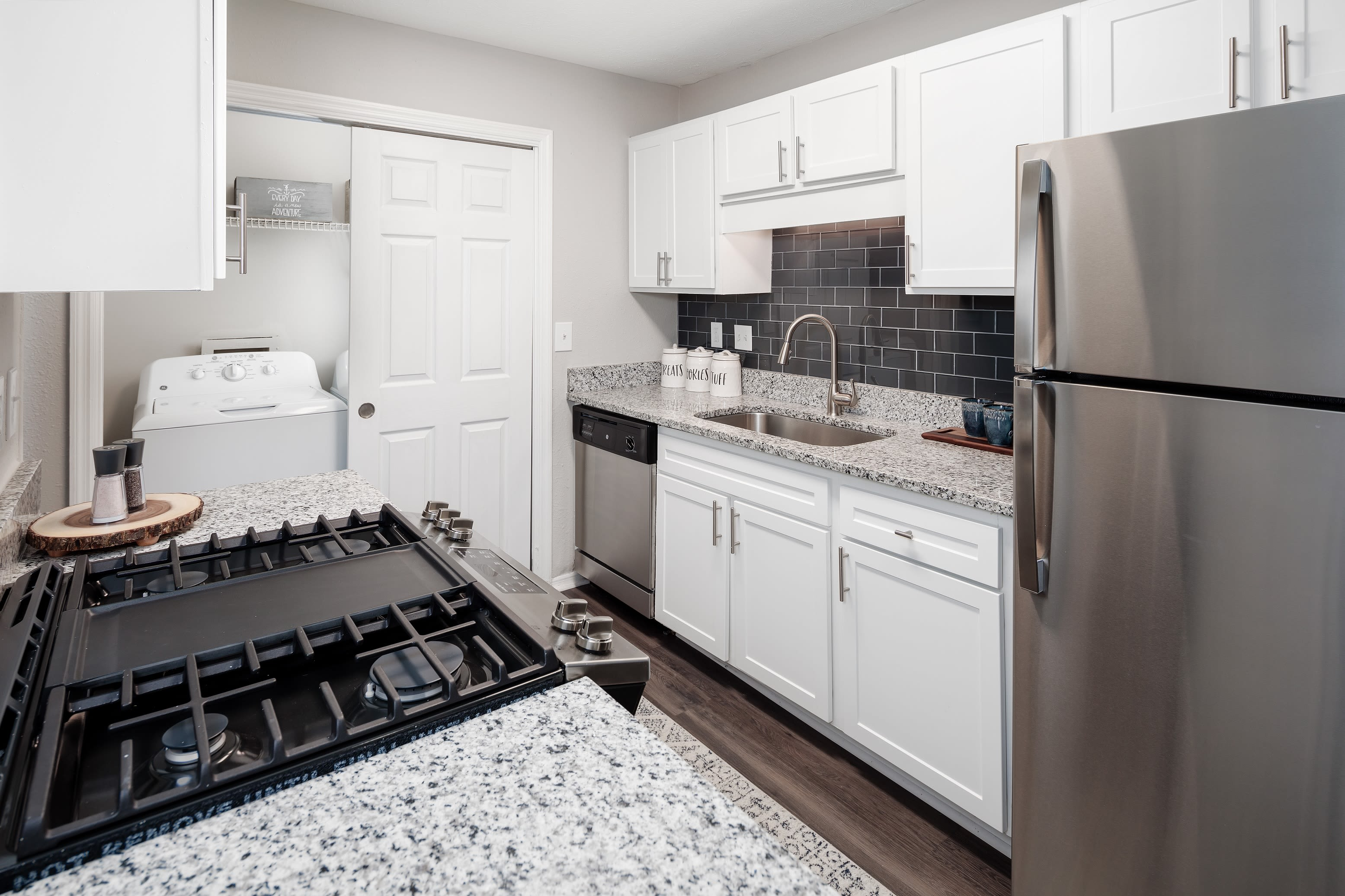 Granite countertops, stainless-steel appliances, and a subway tile backsplash in model home's kitchen at The Bentley at Marietta in Marietta, Georgia