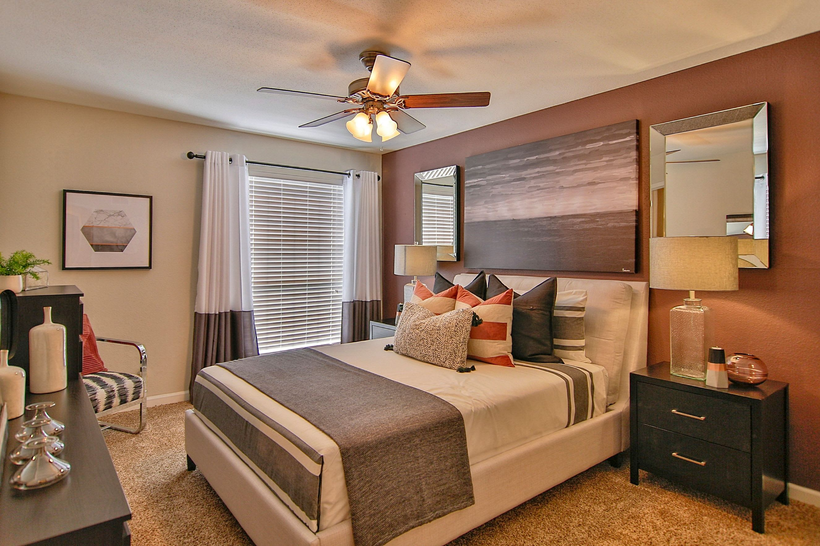 Primary bedroom with a ceiling fan and plush carpeting in a model apartment at Allegro on Bell in Antioch, Tennessee