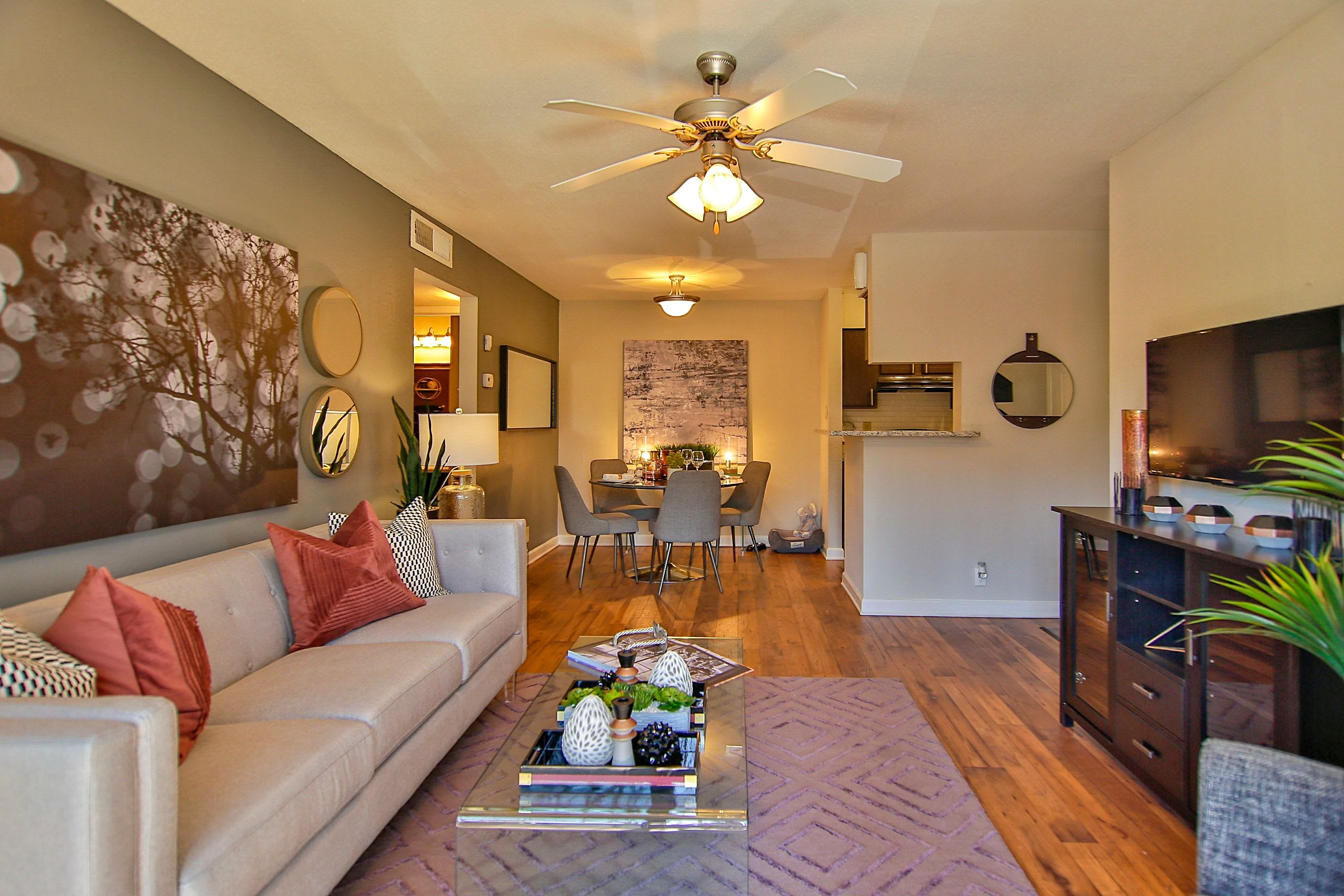 Model home's living area with a ceiling fan and an accent wall at Allegro on Bell in Antioch, Tennessee