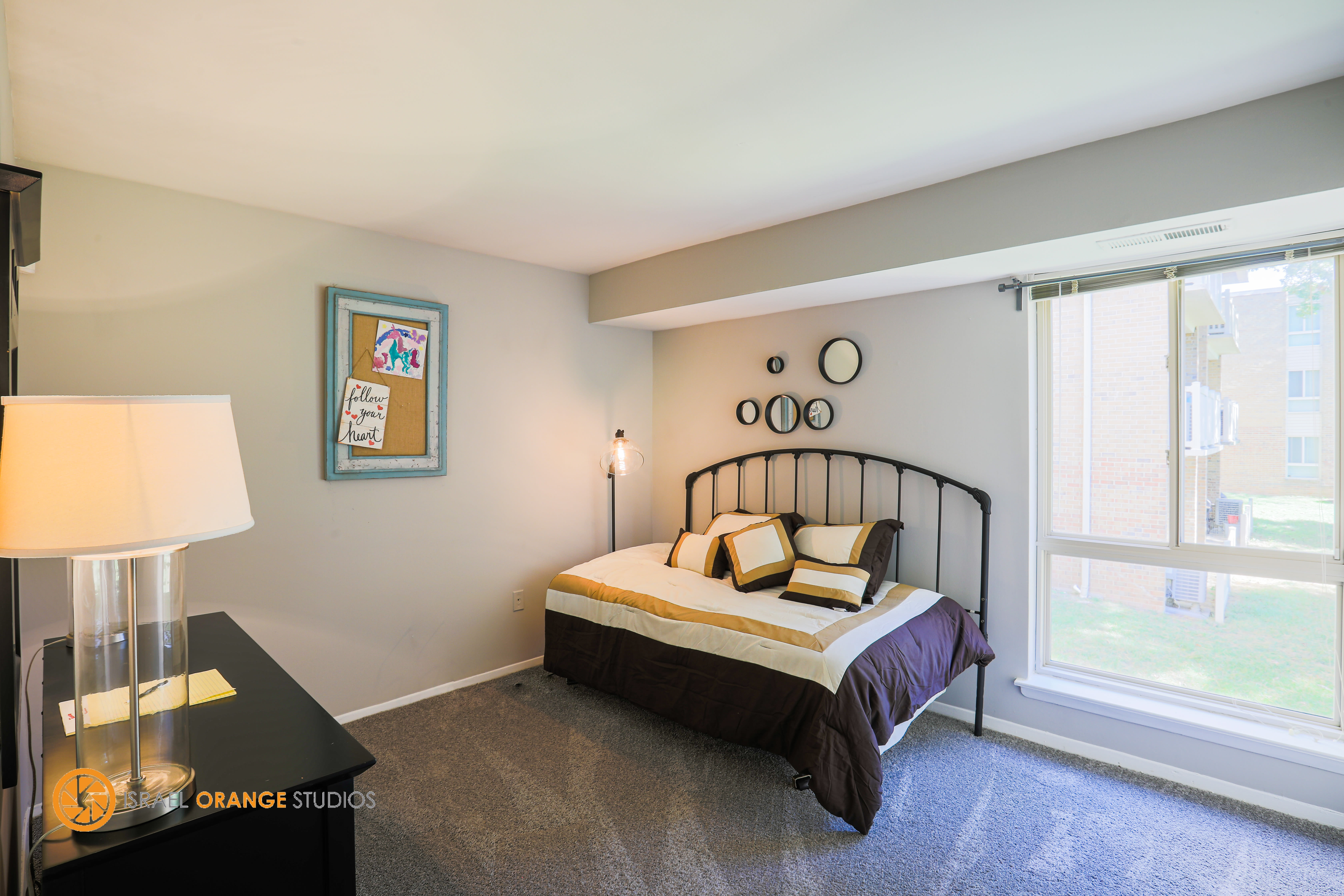 Bedroom next to a large window at The Glendale Residence in Lanham, Maryland