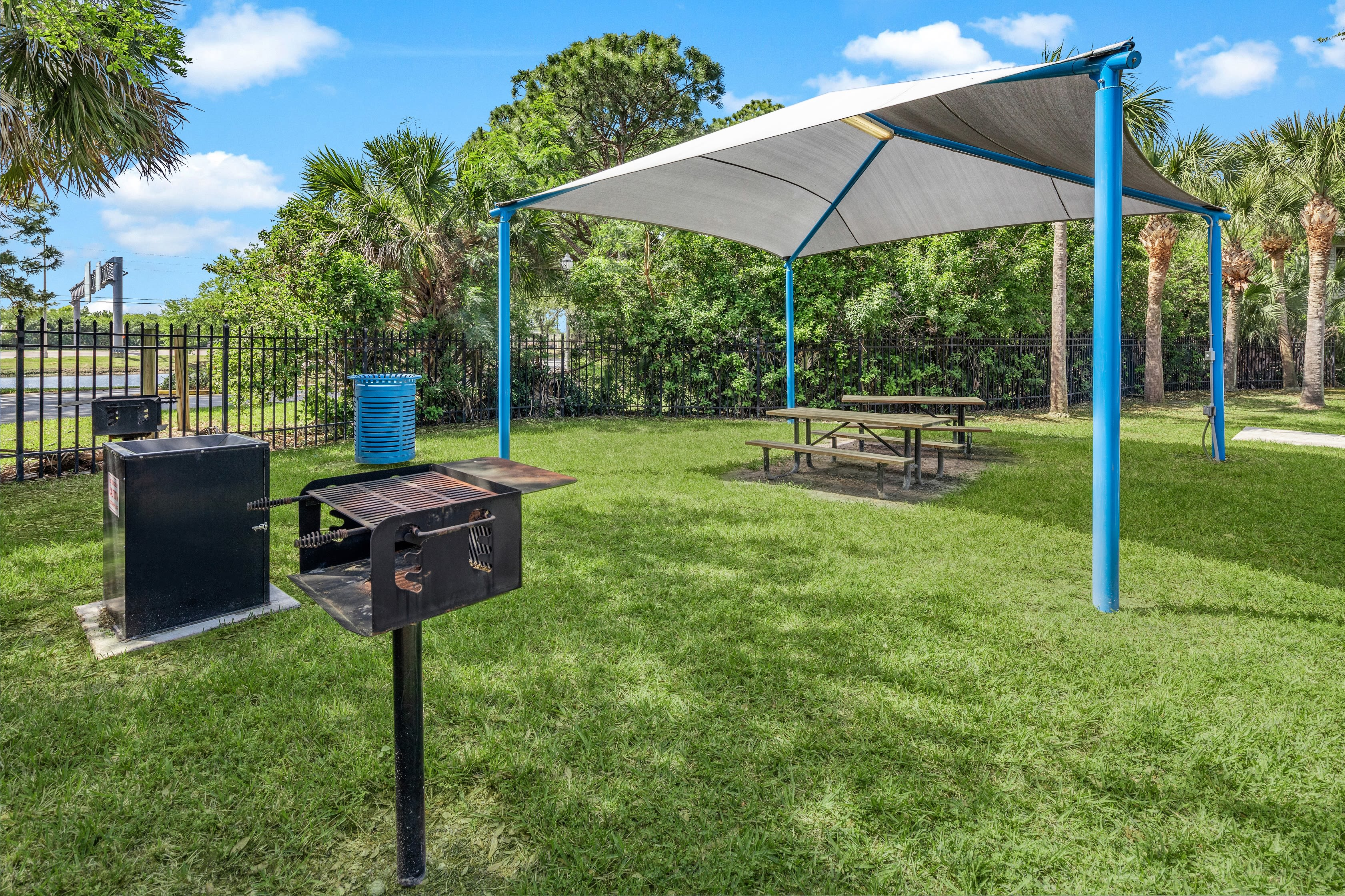 An shaded apartment picnic area with a grill at Fairways at Feather Sound in Clearwater, FL