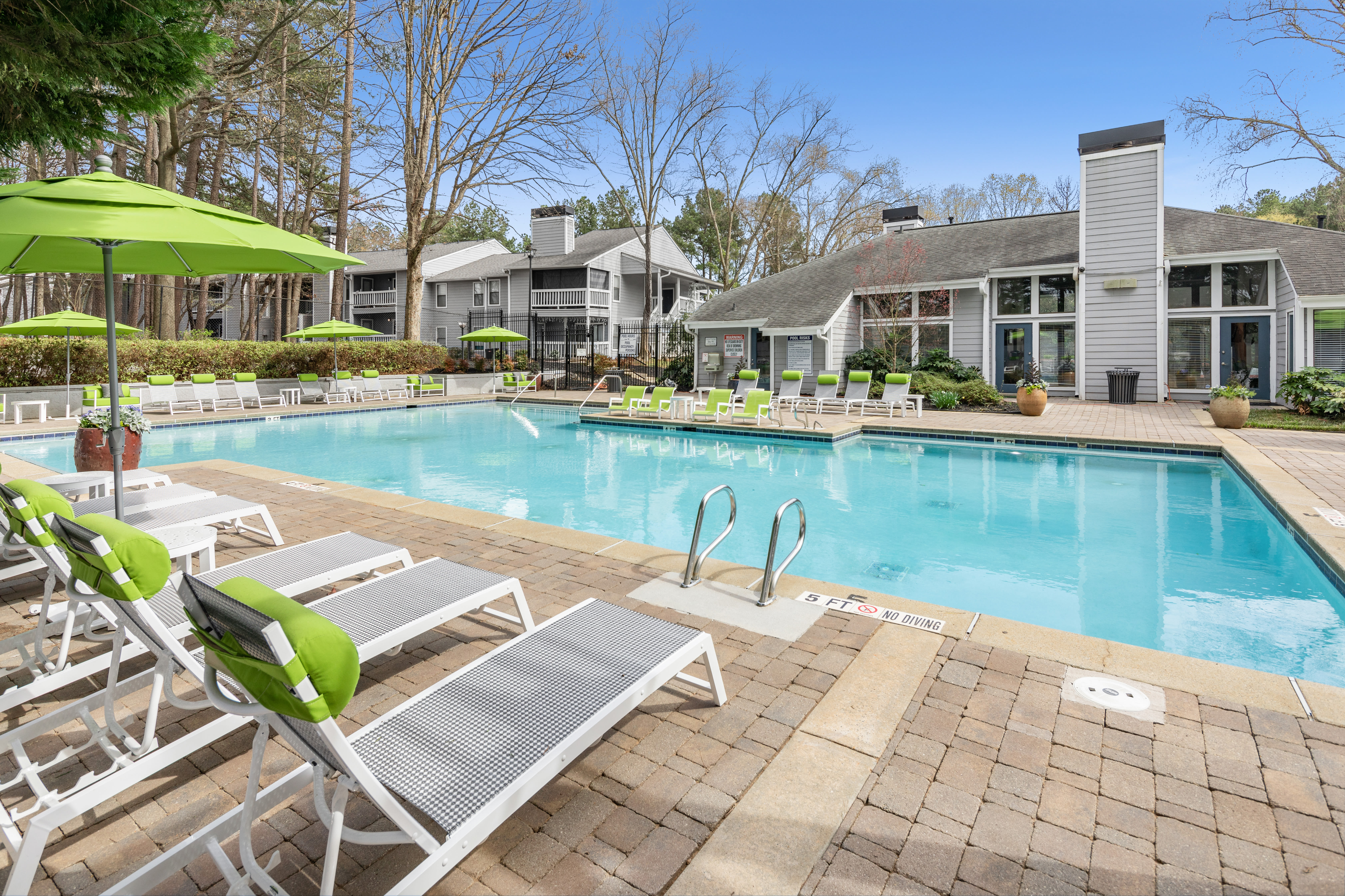 Resort-style swimming pool surrounded by chaise lounge chairs and mature trees at The Franklin in Marietta, Georgia