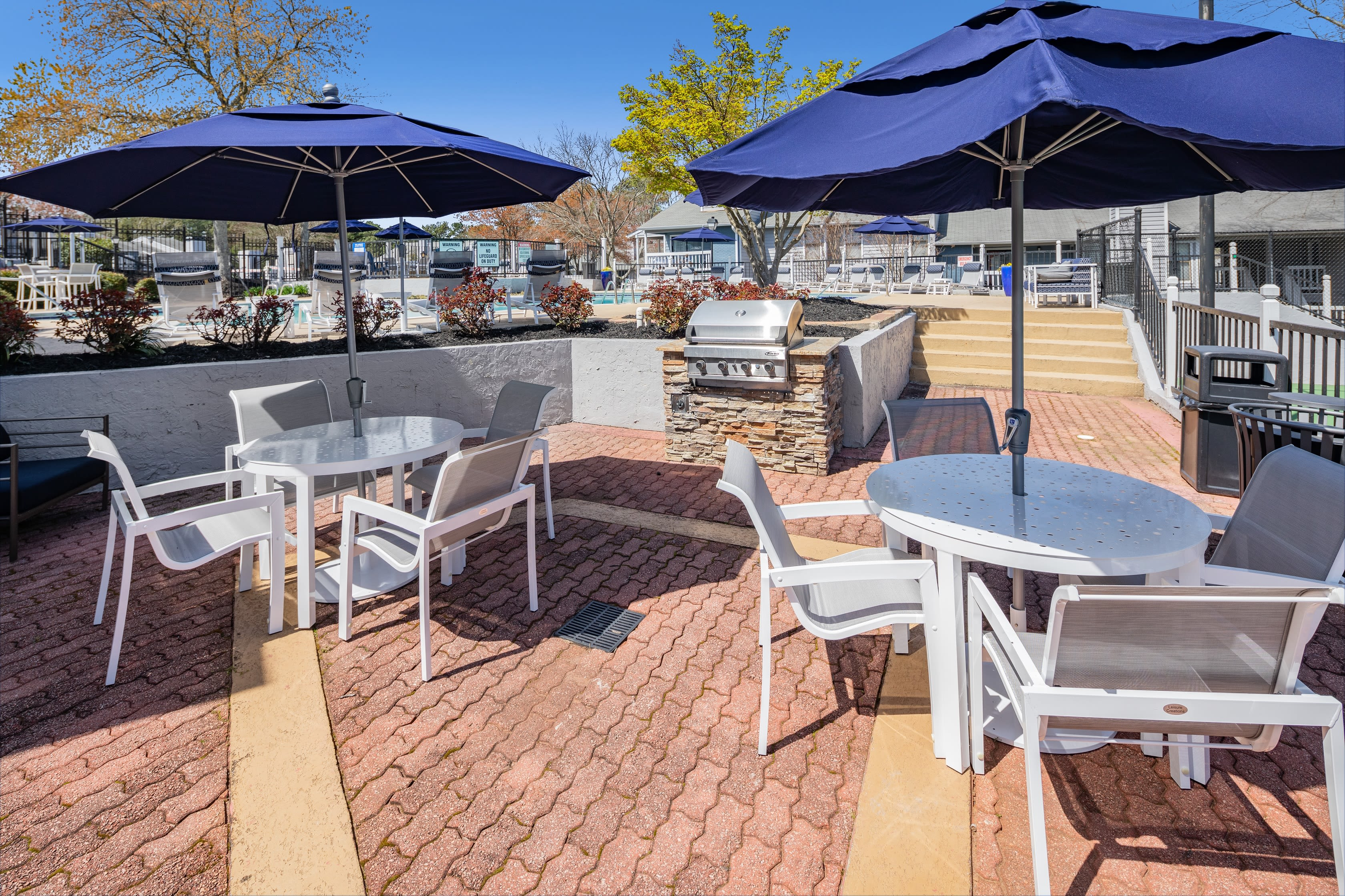 Tables with chairs and umbrellas for outdoor seating The Everette at East Cobb in Marietta, Georgia