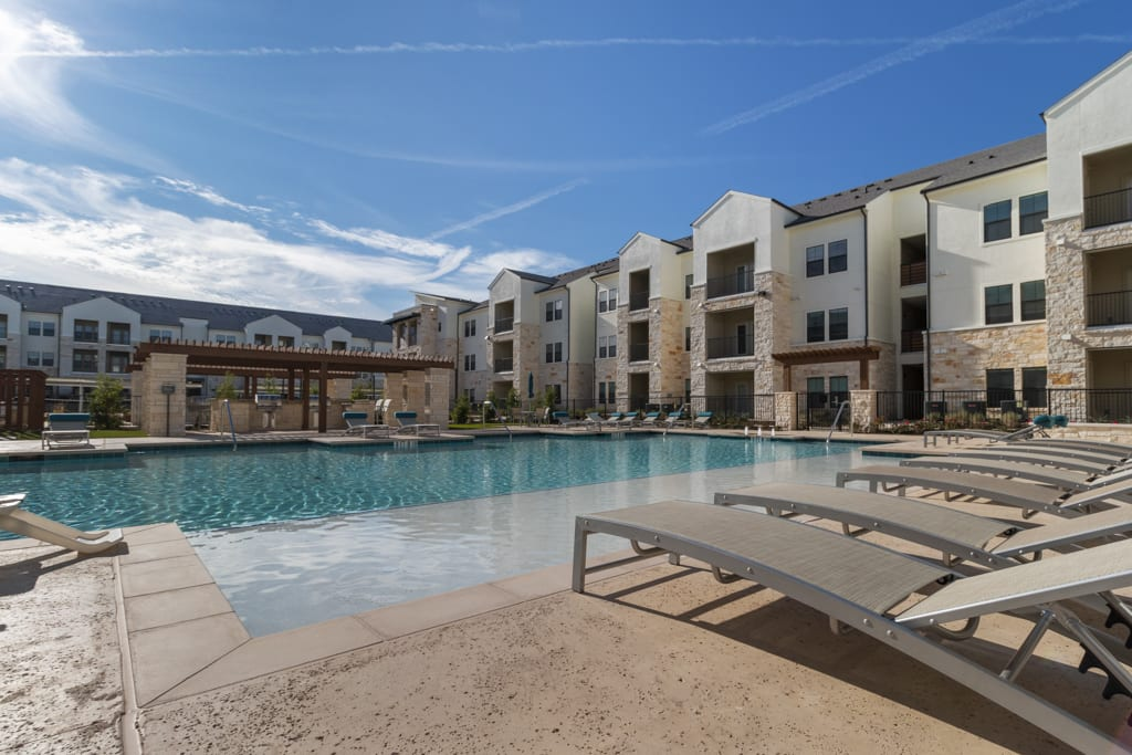Resort style pool with chairs at McCarty Commons in San Marcos, Texas