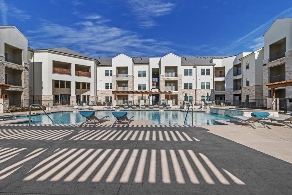 Resort-style swimming pool with lounge chairs at McCarty Commons in San Marcos, Texas