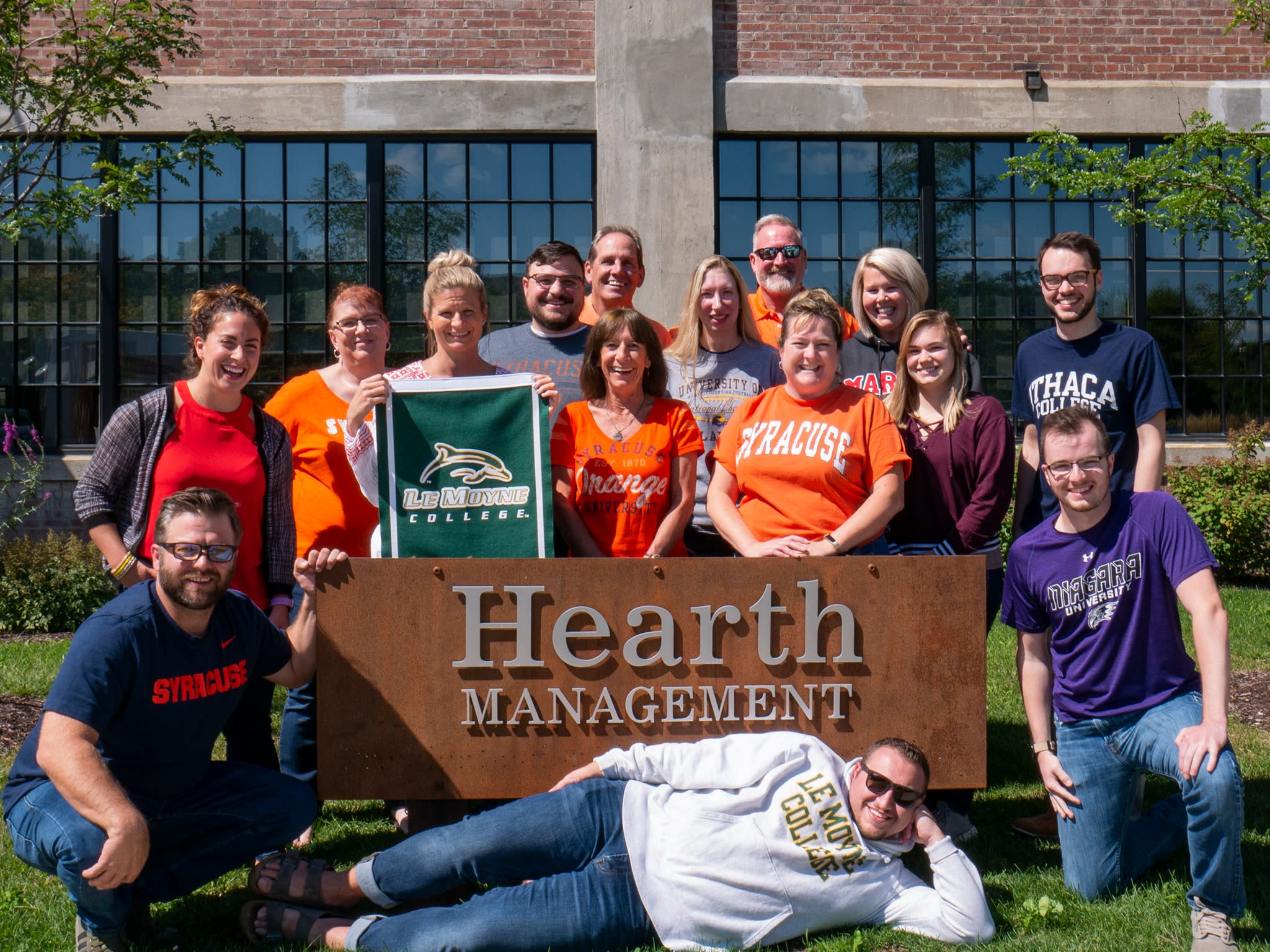 Hearth Management team members in front of our sign