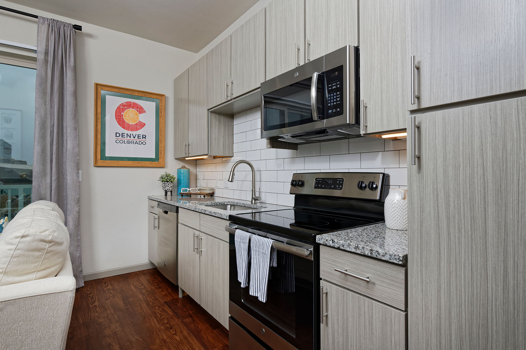 Clean and minimalistic kitchen with black appliances at Civic Lofts in Downtown Denver, CO