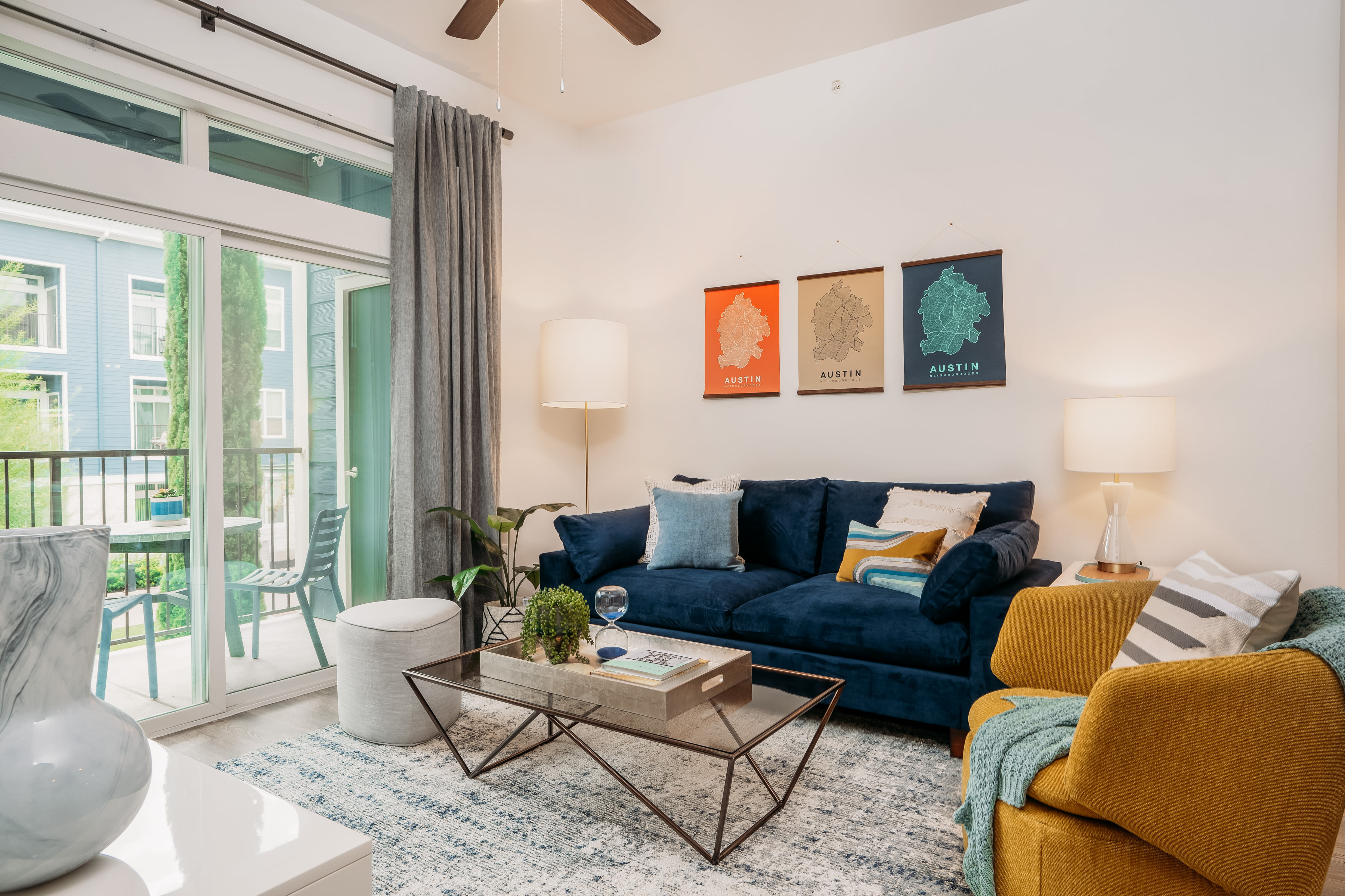 Spacious furnished living room with a glass slider door at Lakeshore Pearl in Austin, Texas