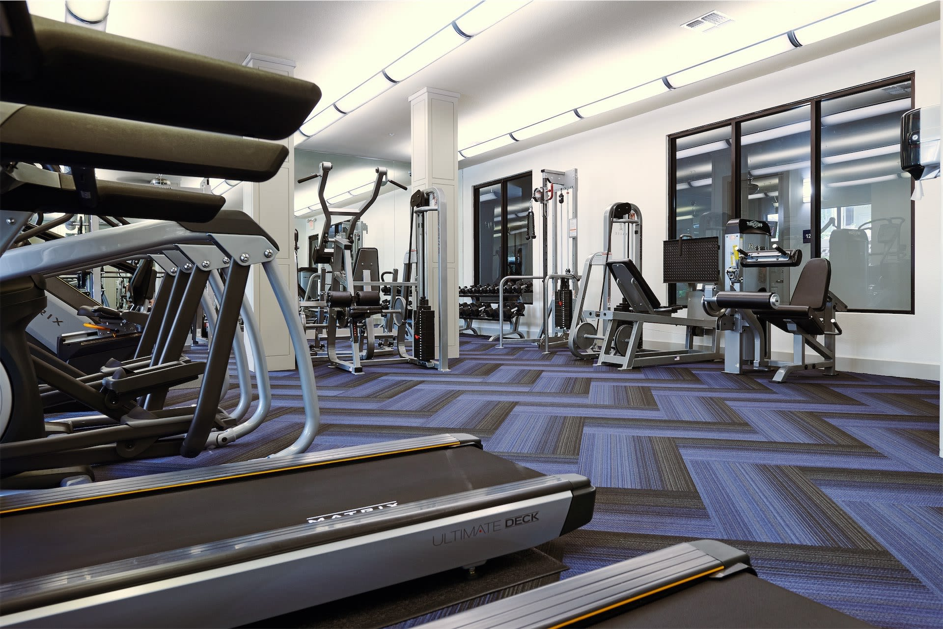 Treadmill close-up with carpeted gym at Seville Uptown in Dallas, Texas