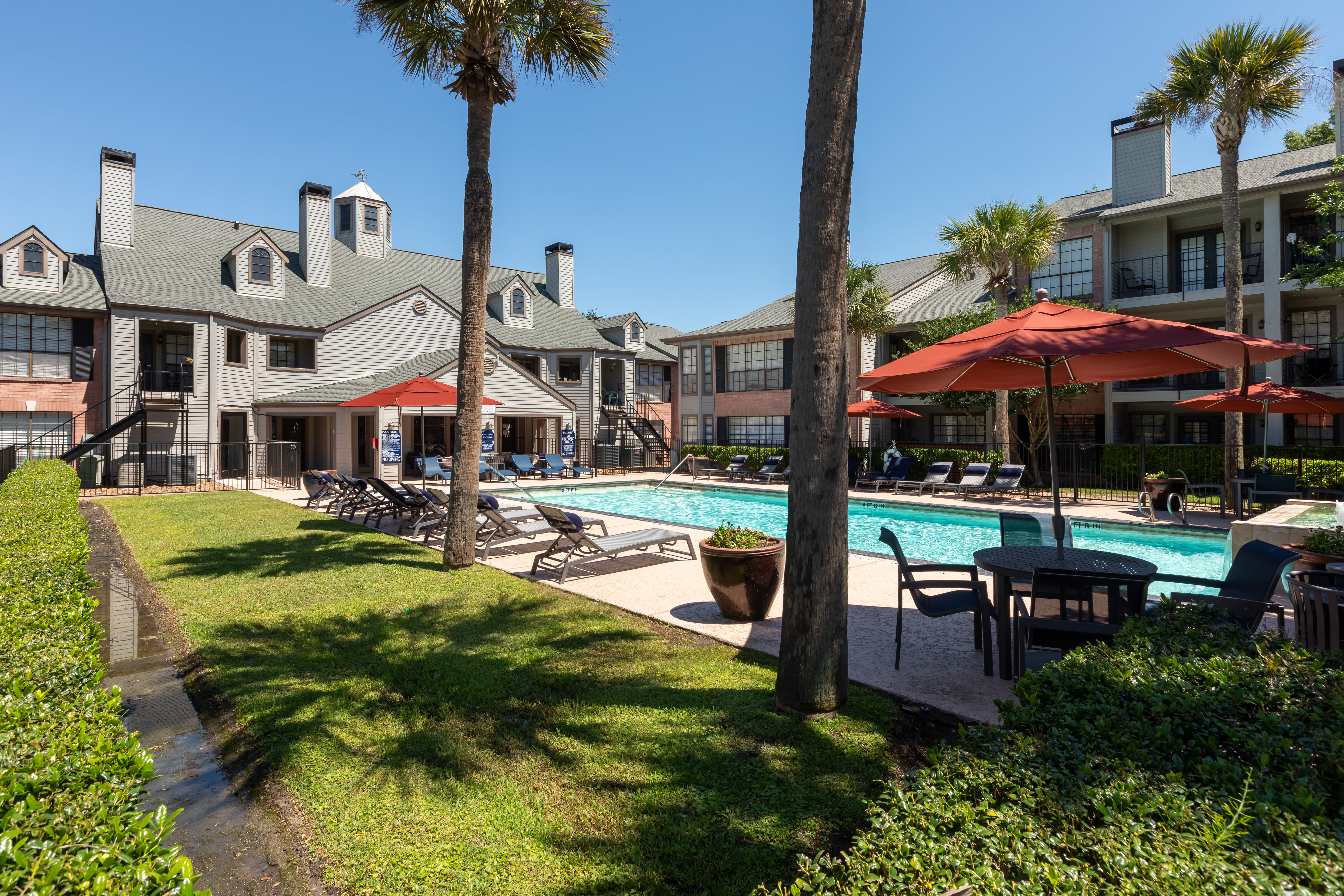 A beautiful pool surrounded by a lush landscape at McAlister in Webster, Texas