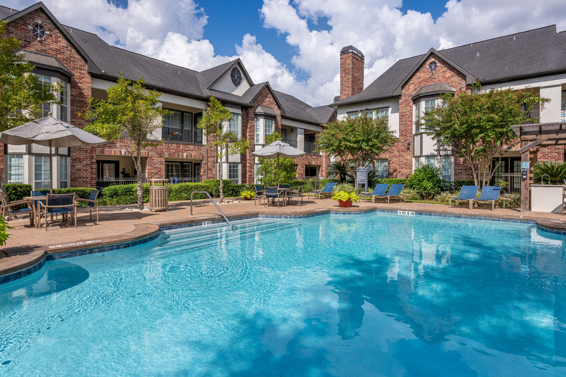 Large pool with apartments behind at Marquis on Memorial in Houston, Texas
