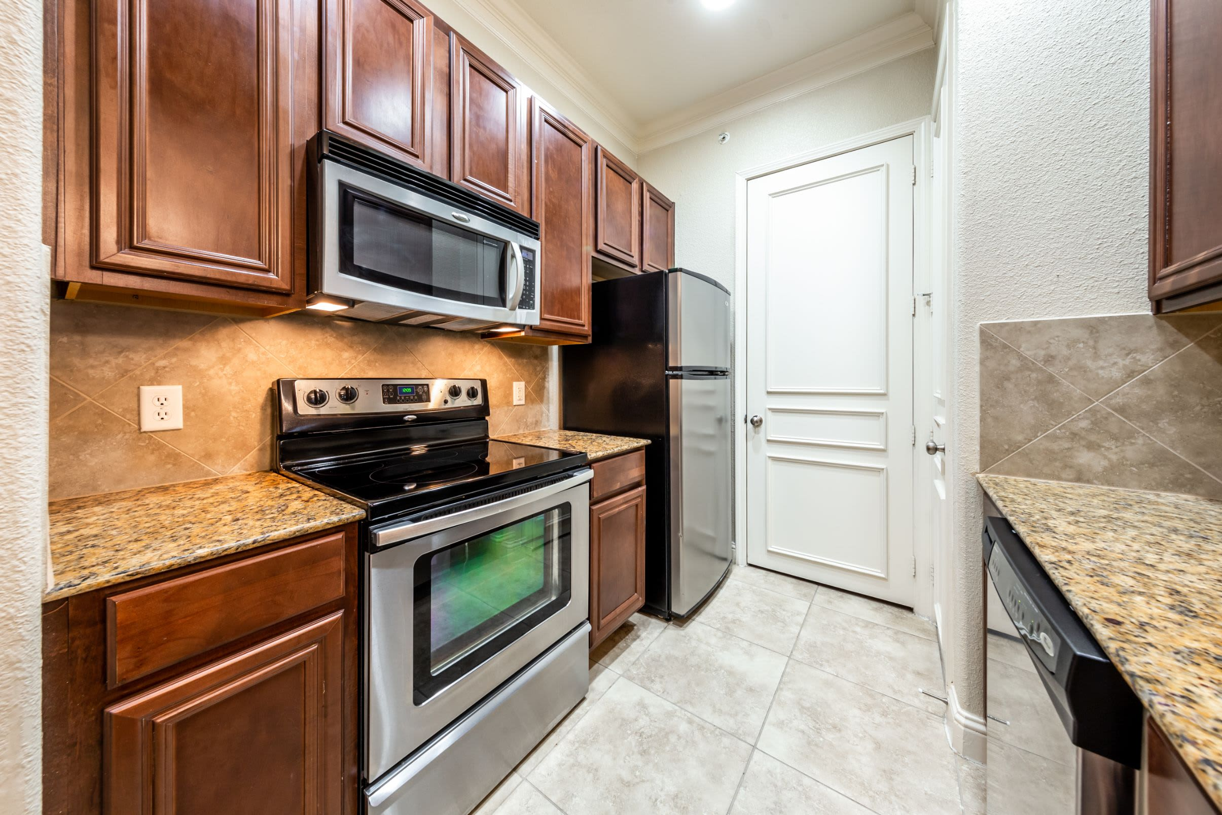 Kitchen with granite style countertops at Marquis at TPC in San Antonio, Texas