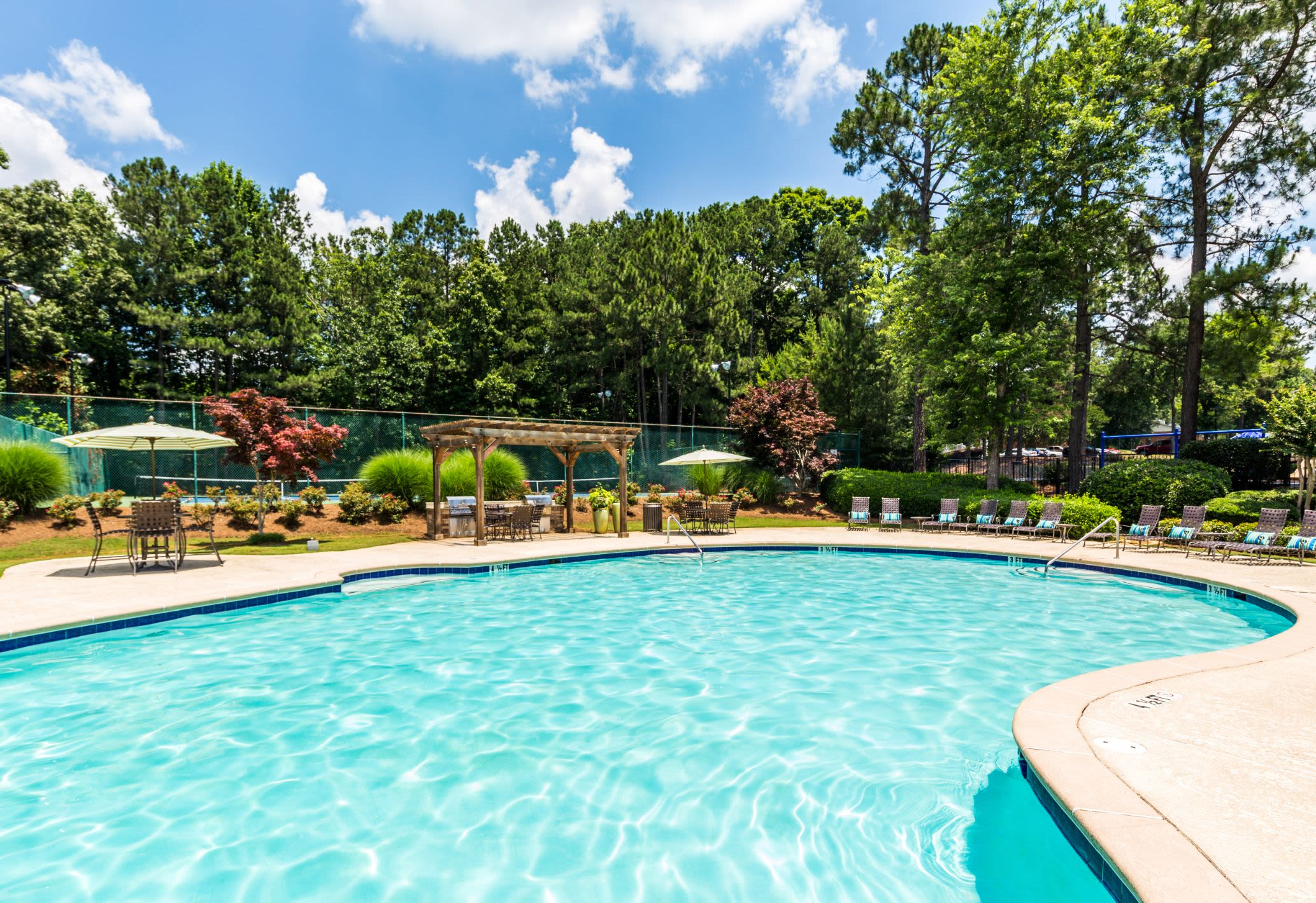 Swimming pool surrounded by trees at Marquis at Perimeter Center in Atlanta, Georgia
