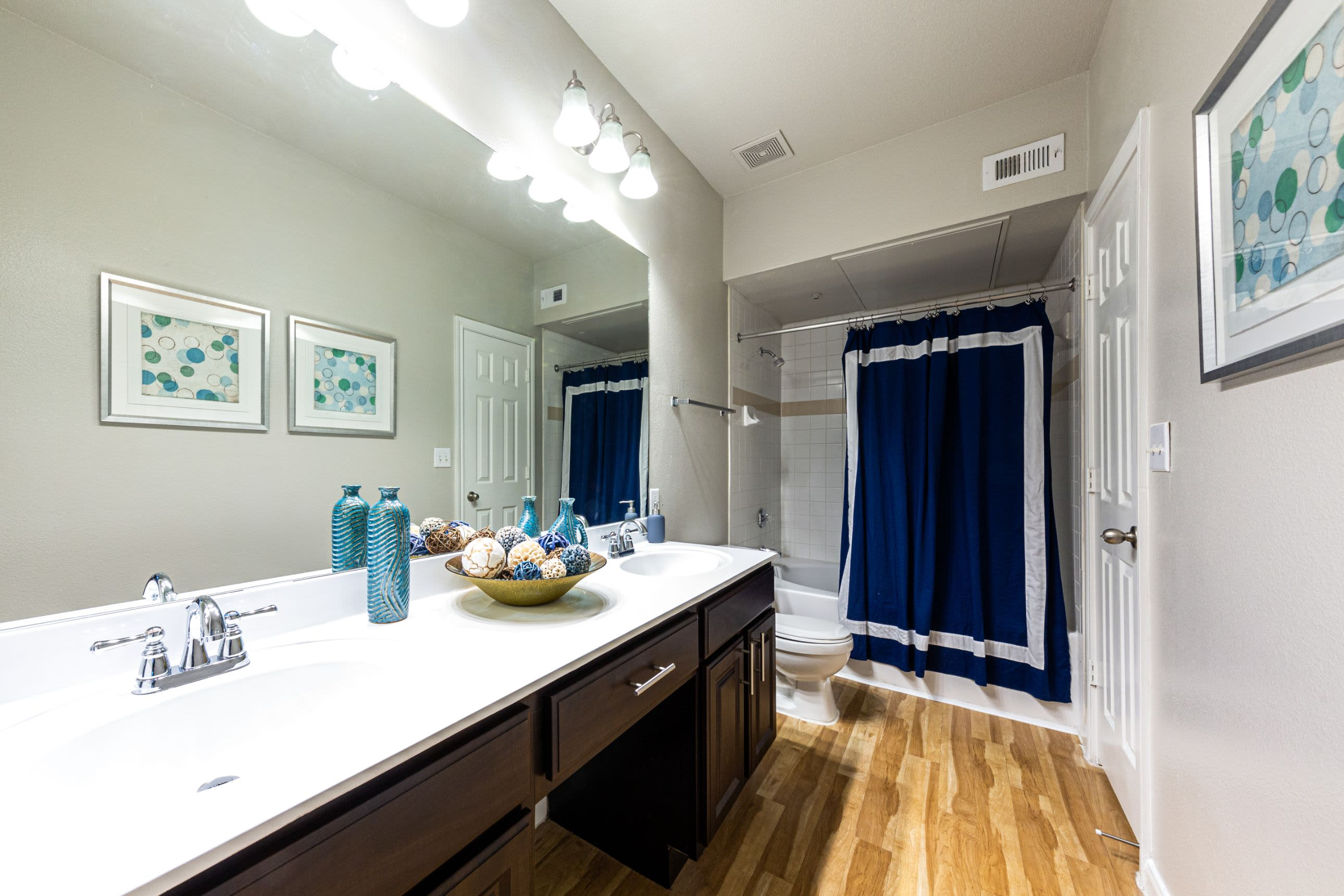 Bathroom with dark cabinets and white counters at Marquis at Westchase in Houston, Texas