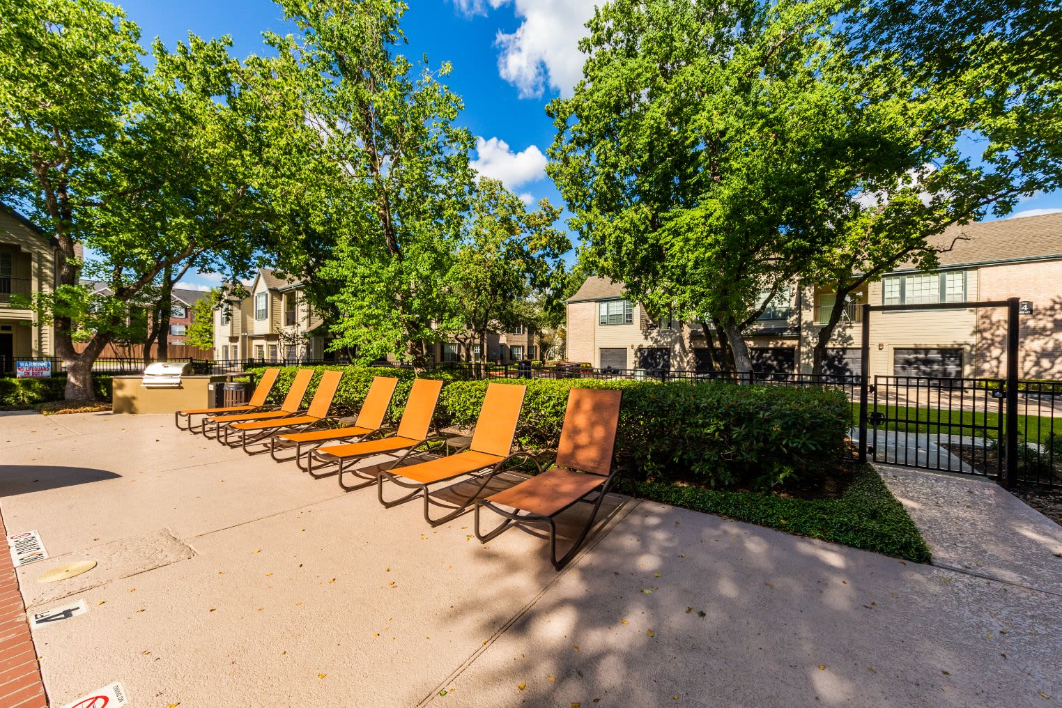 Sun chairs next to pool at Marquis at Westchase in Houston, Texas