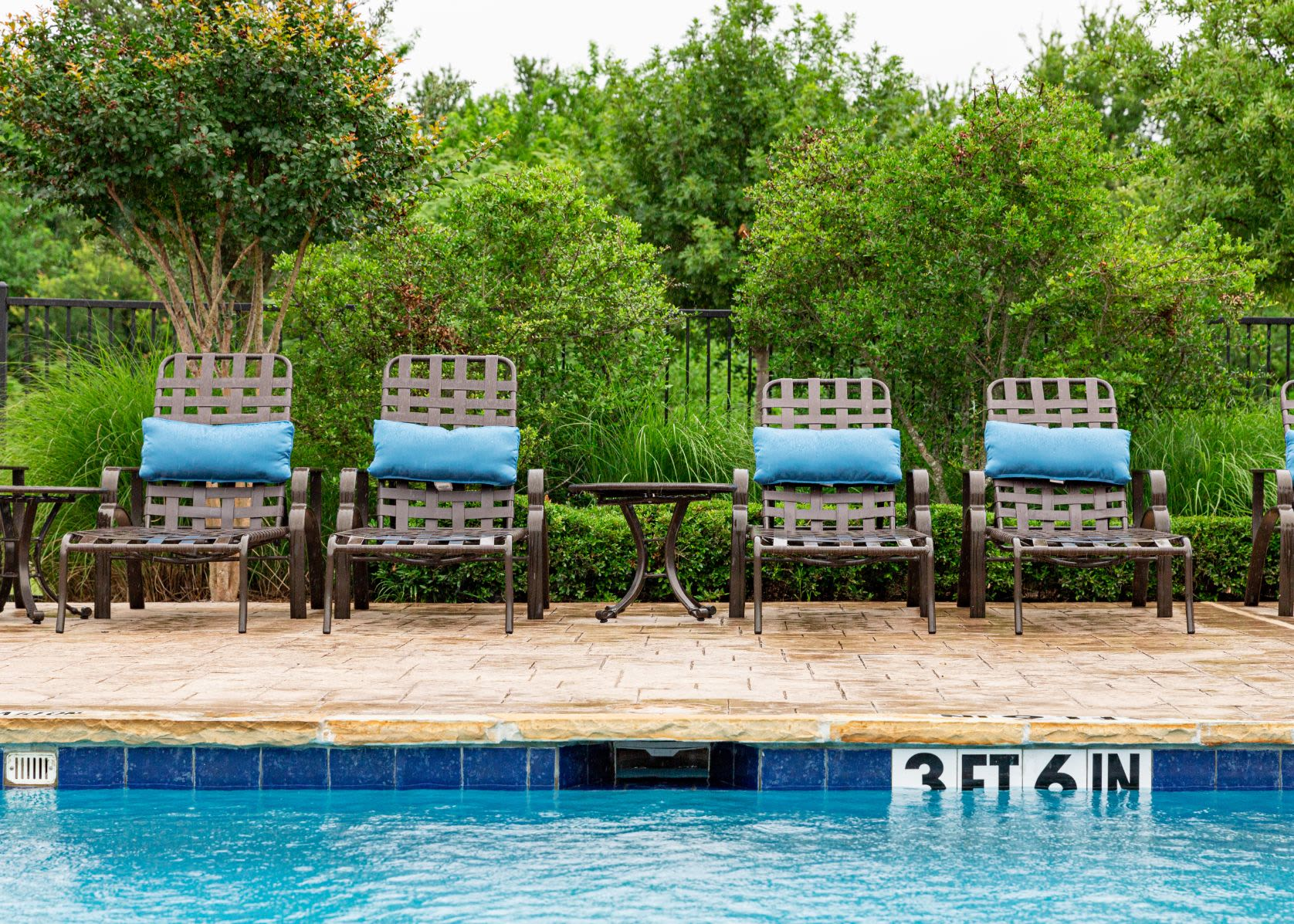 Community pool with sun chairs at Marquis Rockwall in Rockwall, Texas