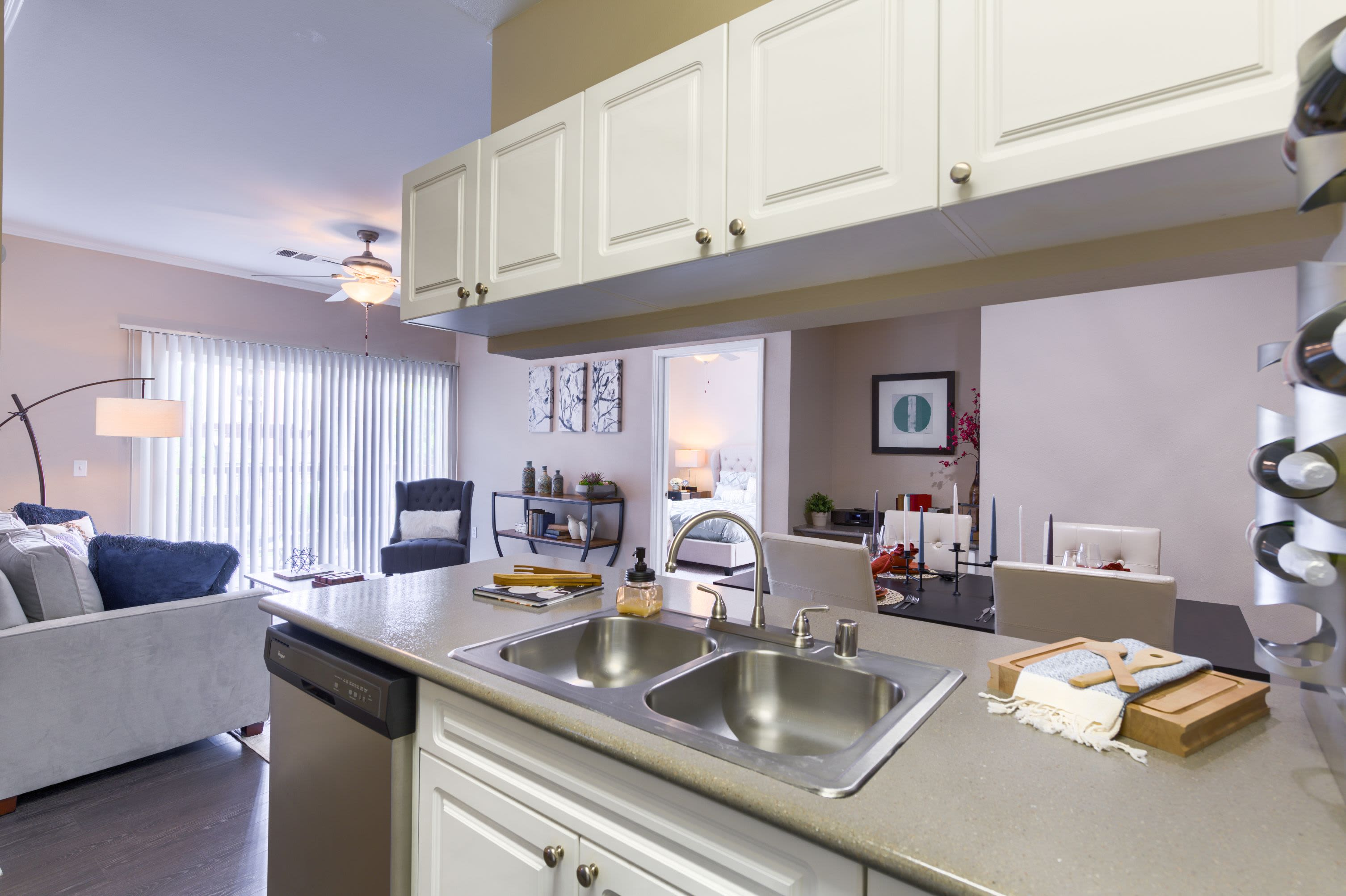 Modern kitchen adjacent to living area at Whisper Creek Apartment Homes in Lakewood, Colorado