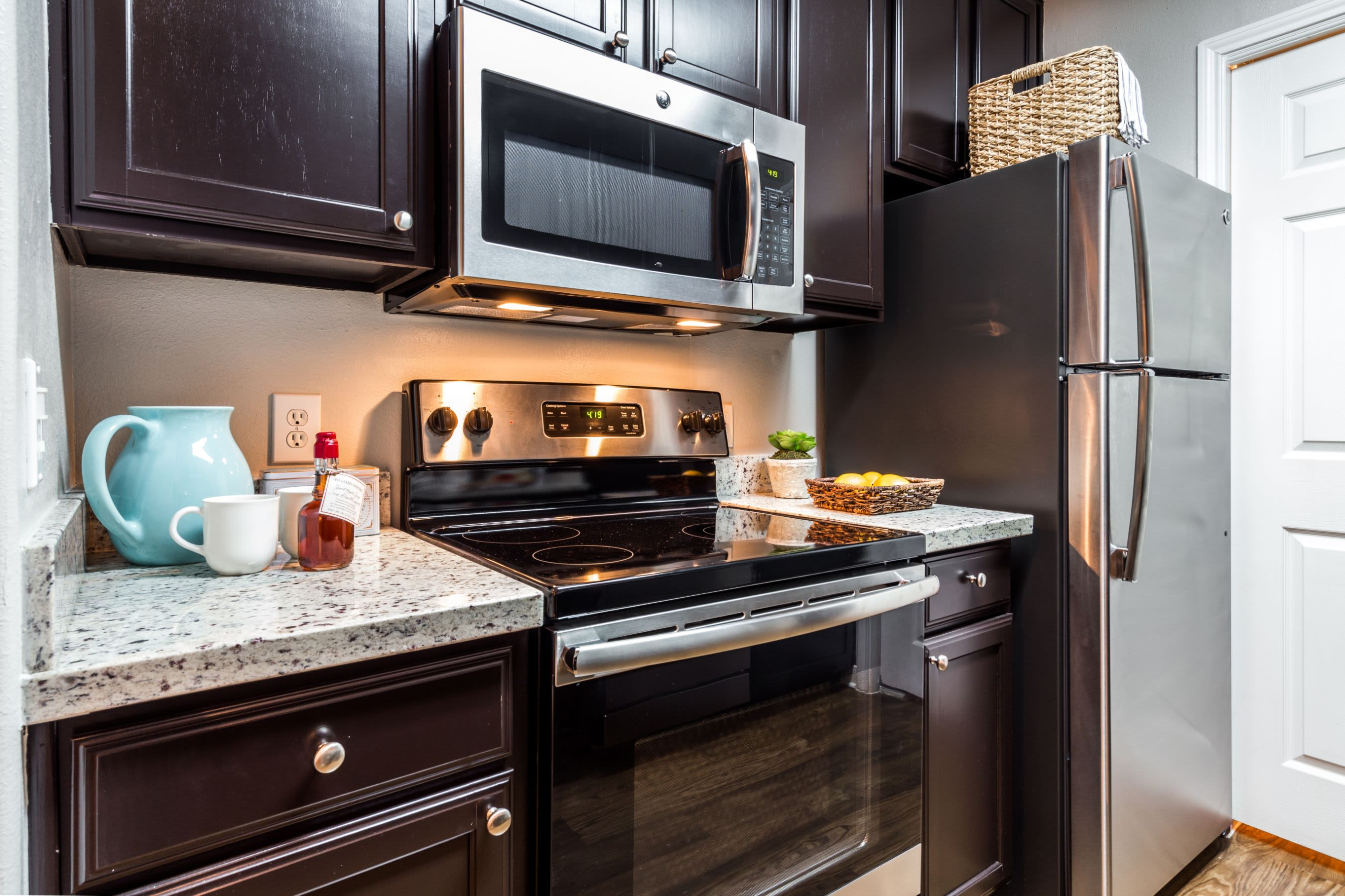 Modern kitchen with wood style floors at Marquis on Westheimer in Houston, Texas