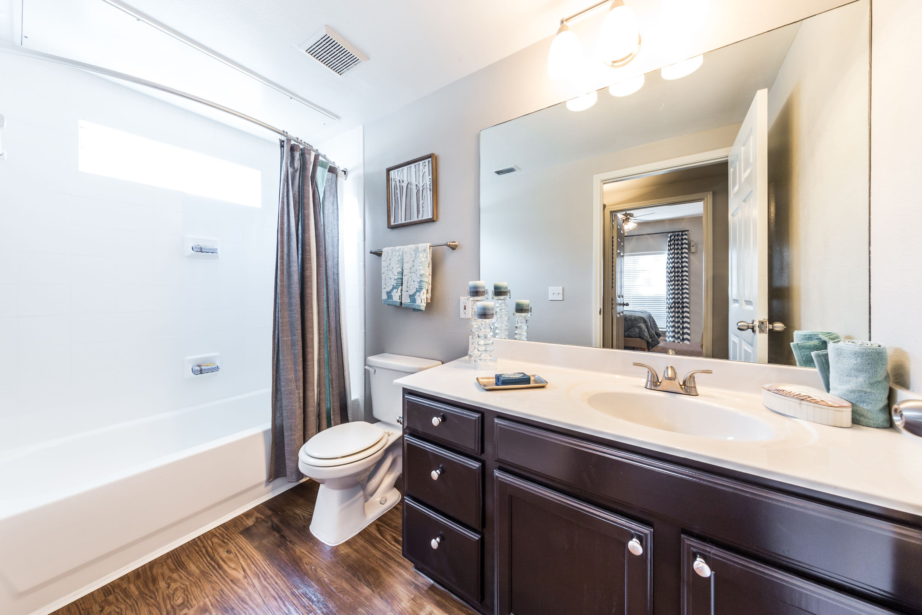 Bathroom with dark cabinets and white countertops at Marquis on Westheimer in Houston, Texas