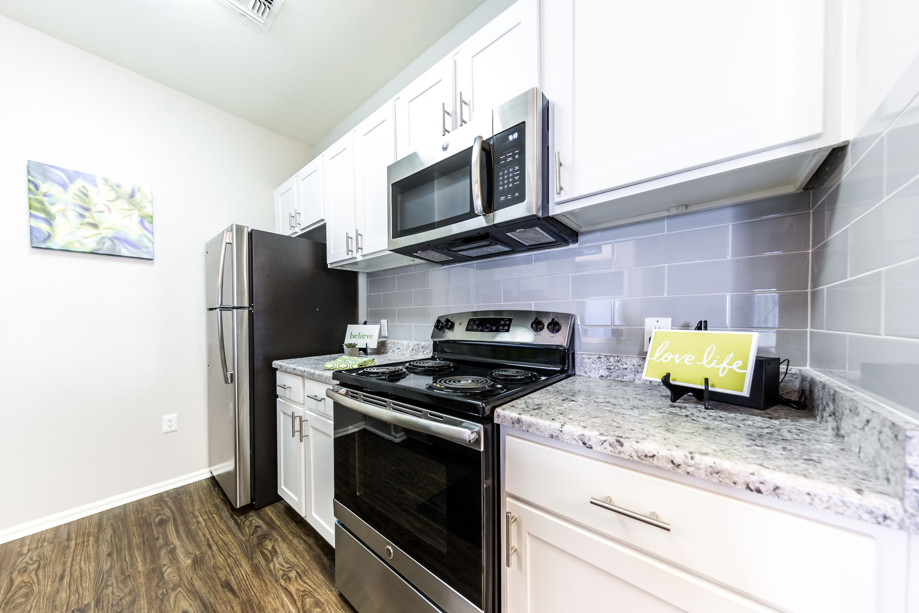 Fully equipped kitchen with white cabinets at Marquis at Arrowhead in Peoria, Arizona