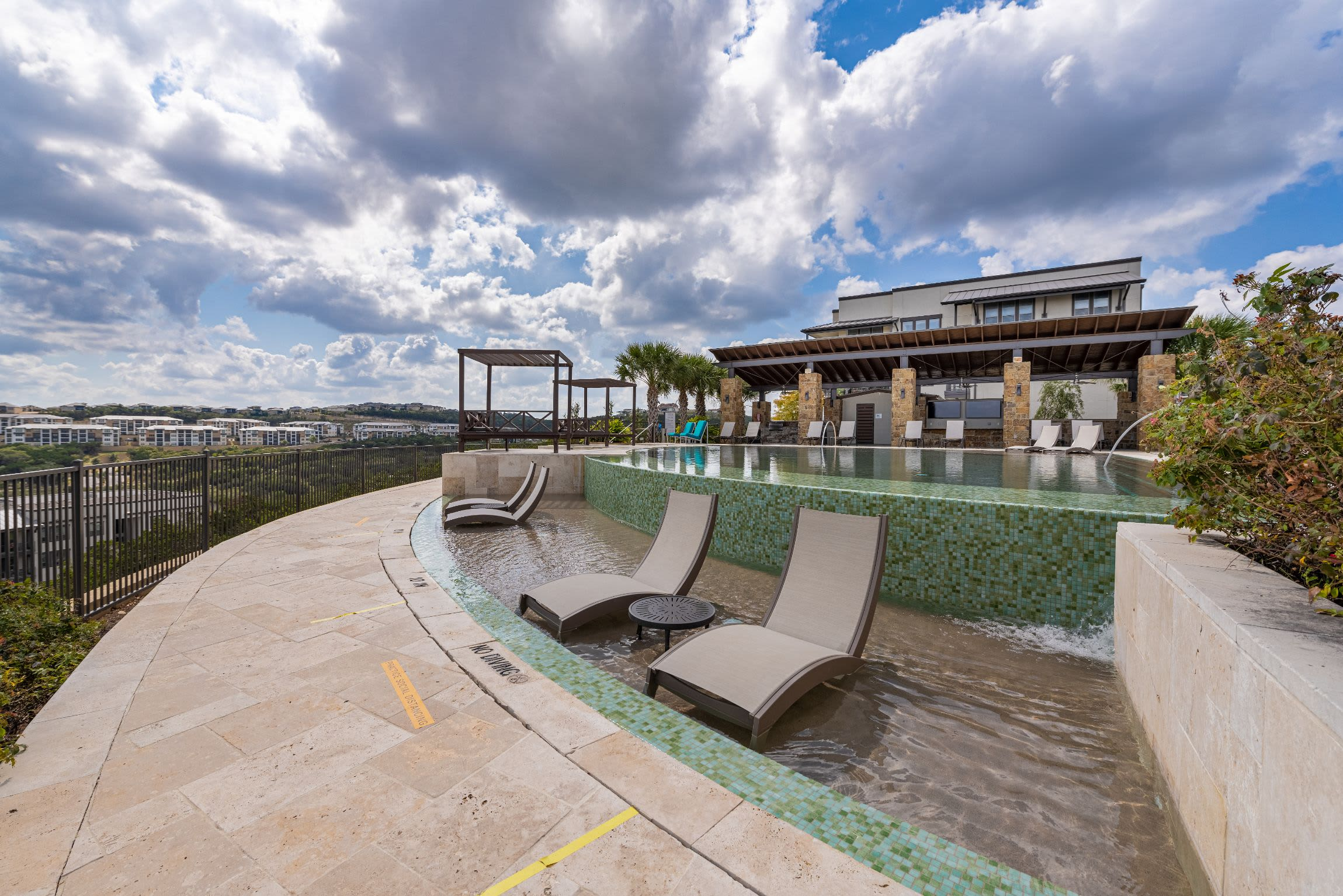 Sun chairs in swimming pool at Marquis Cresta Bella in San Antonio, Texas