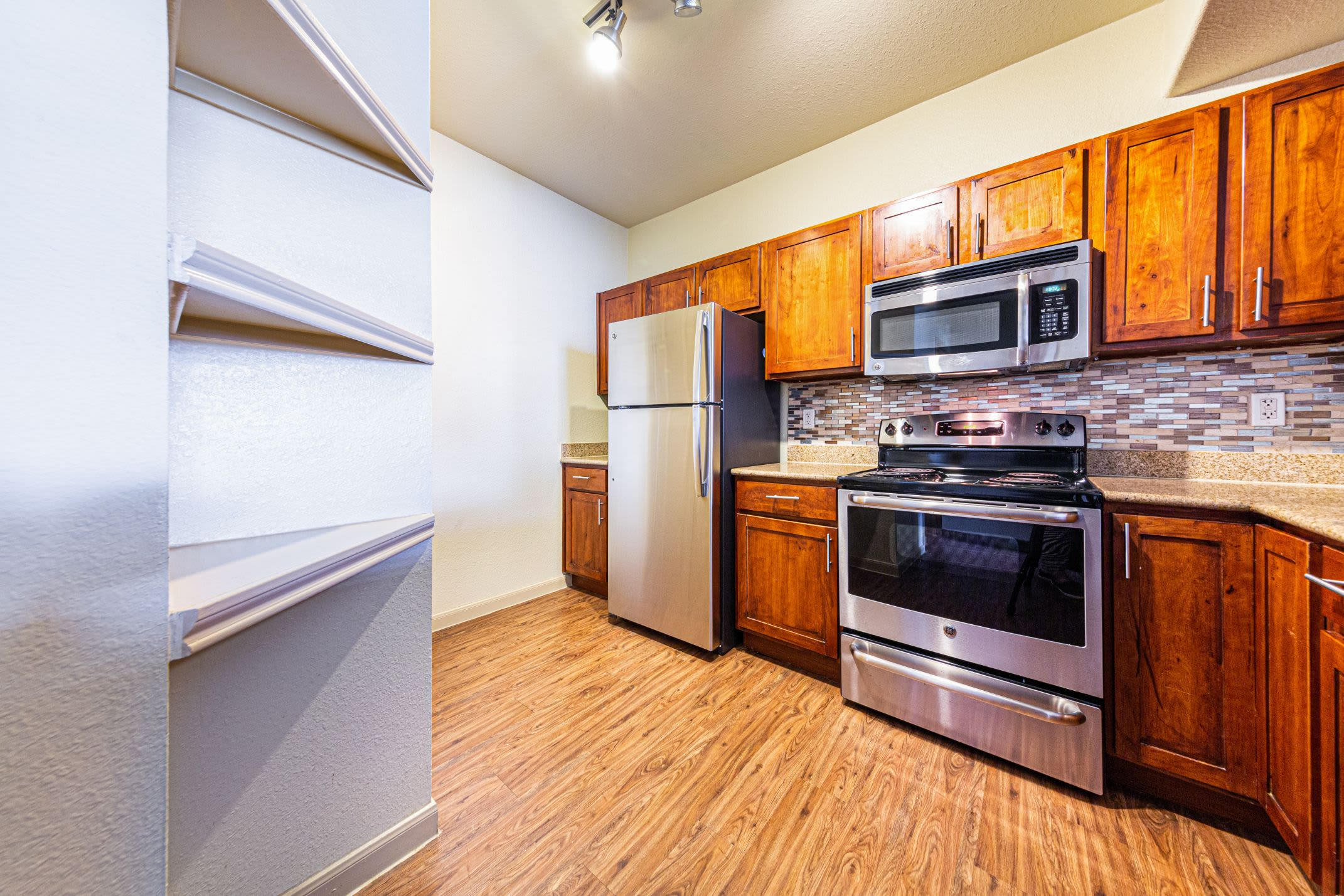 Kitchen with wood style floors at Marquis Grand Lakes in Richmond, Texas