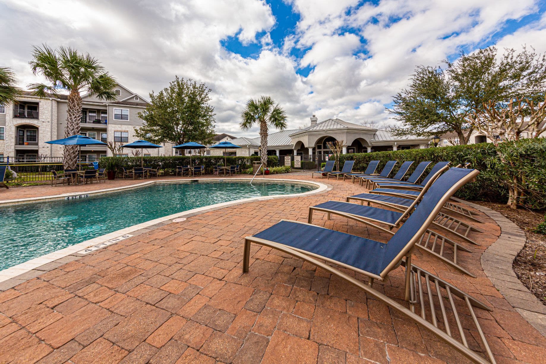 Sun chairs next to pool at Marquis Grand Lakes in Richmond, Texas