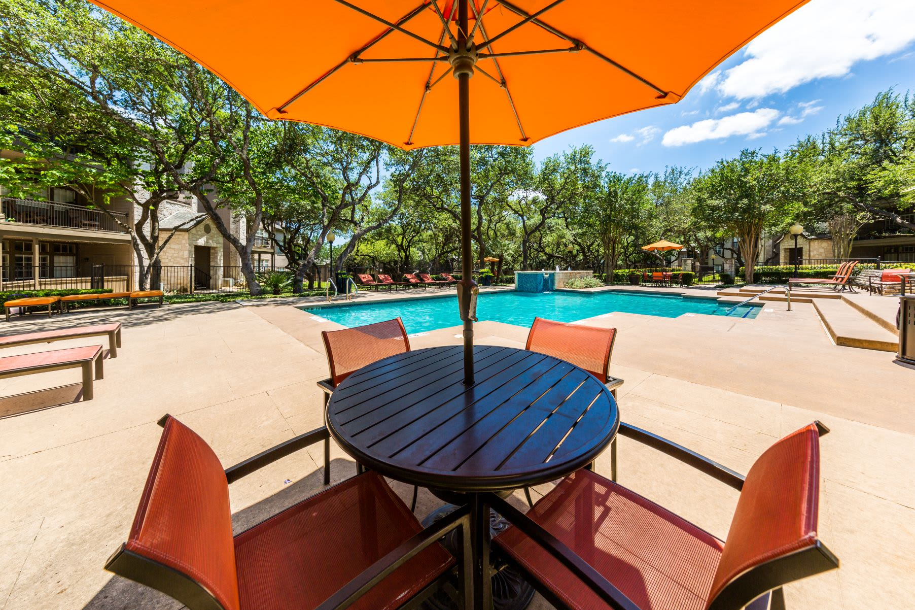 Table and chairs by the pool at Marquis at Deerfield in San Antonio, Texas