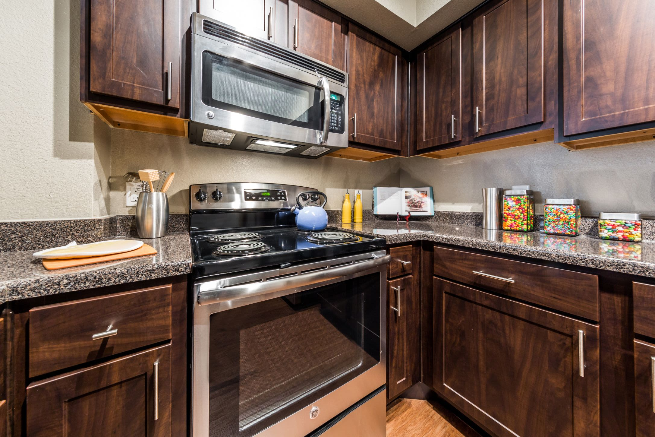 Kitchen with dark colored cabinets at Marquis at Deerfield in San Antonio, Texas