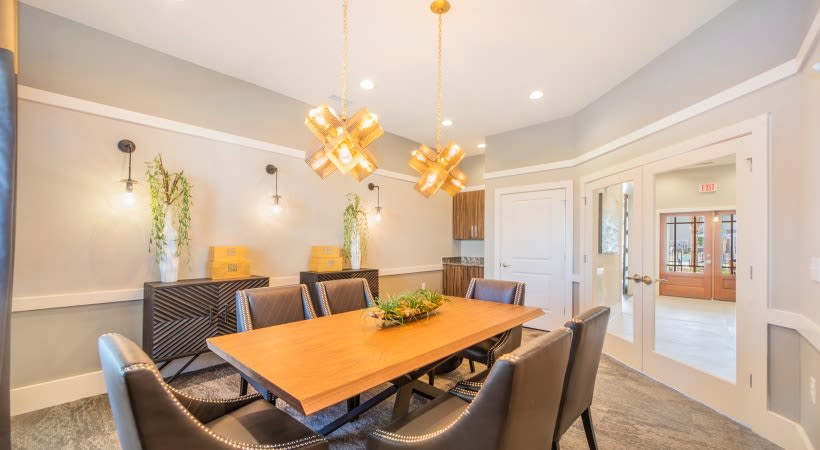 Modern dining area with wood table at The Isaac in Summerville, South Carolina