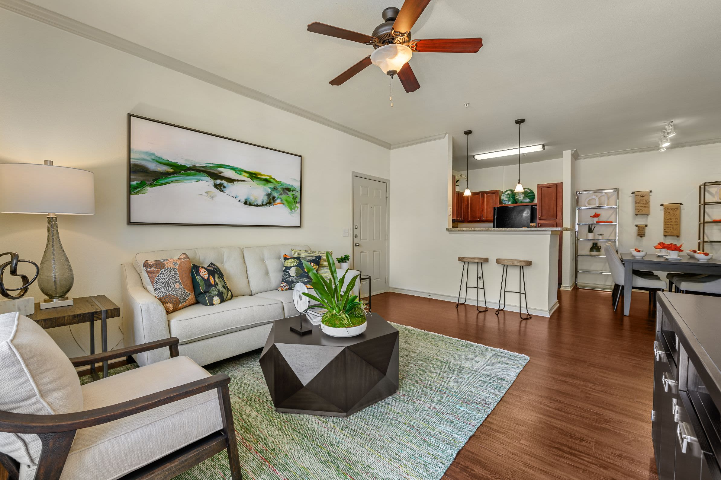 Living room with wood style floors and a large rug at Marquis Lakeline Station in Austin, Texas