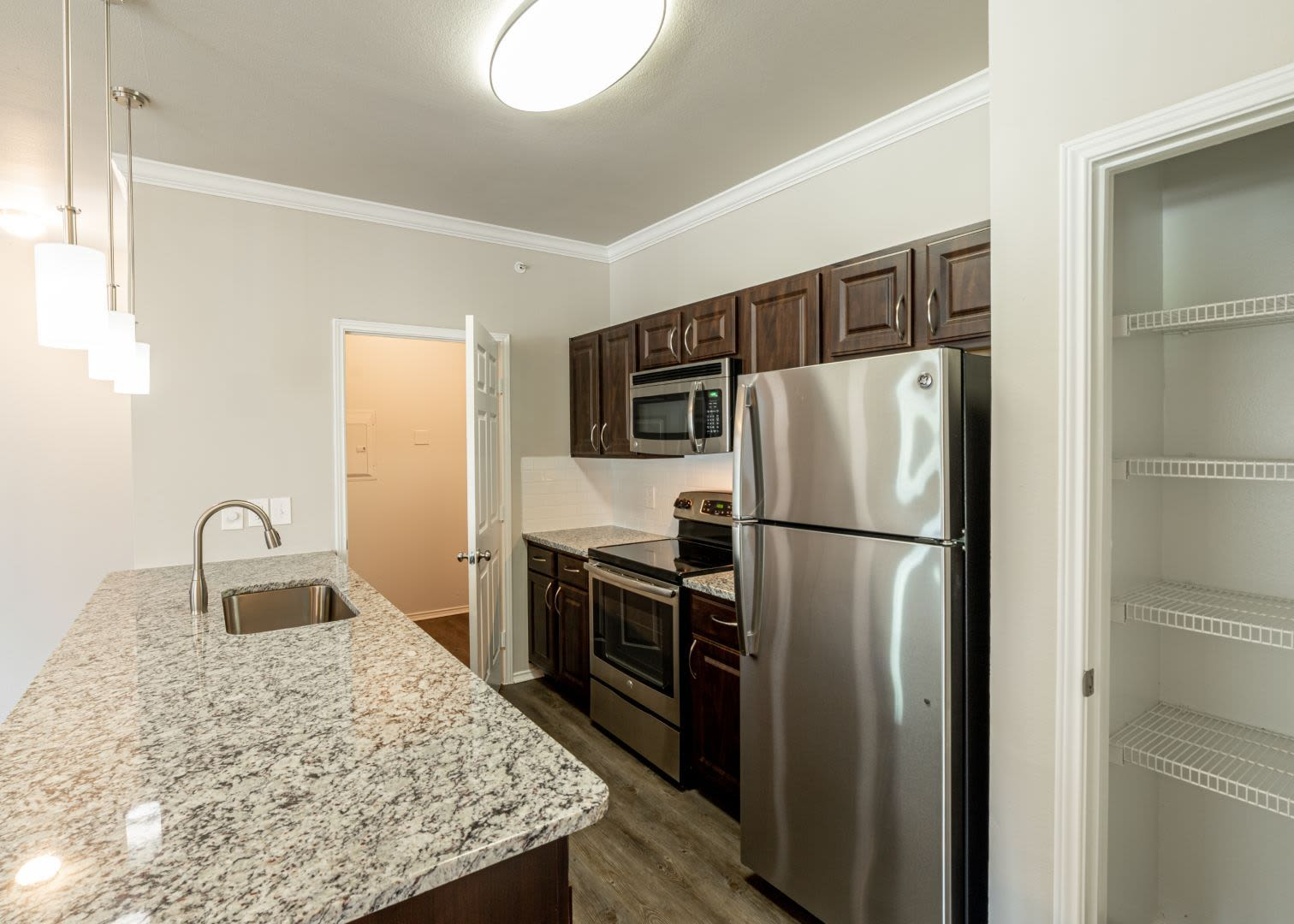 Modern kitchen with granite style countertops at Marquis at Stonebriar in Frisco, Texas
