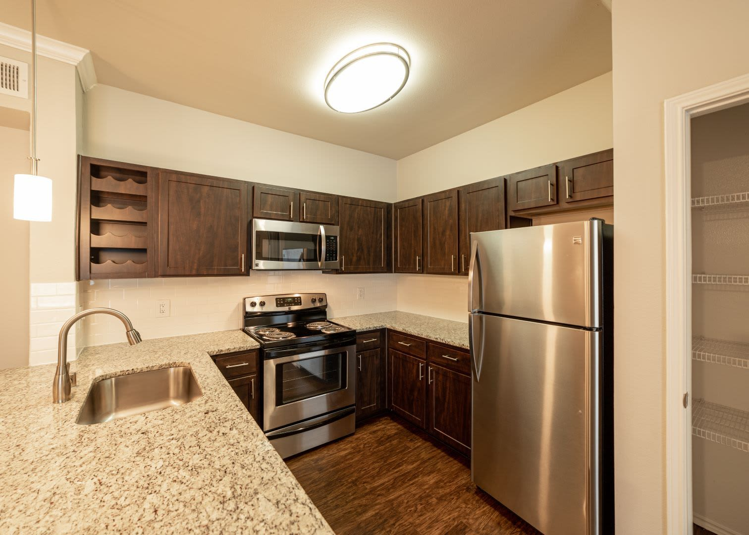 Bright kitchen with wood style floors at Marquis at Stonebriar in Frisco, Texas