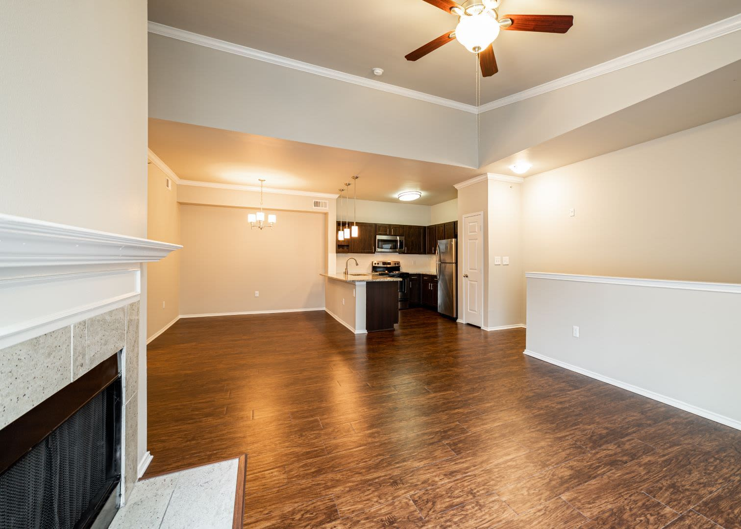 Open living room and dining area with wood style floors at Marquis at Stonebriar in Frisco, Texas