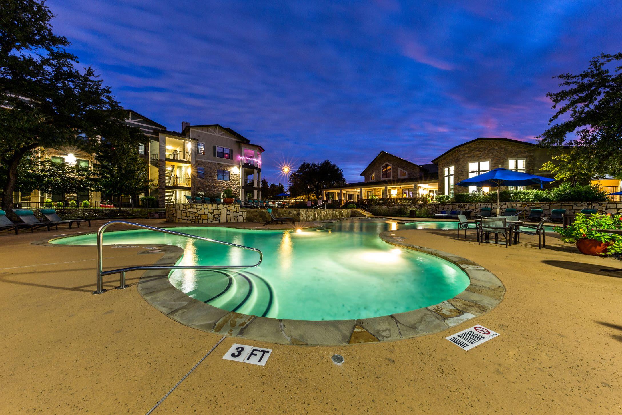 Well lit pool beneath purple skies at Marquis on Lakeline in Cedar Park, Texas