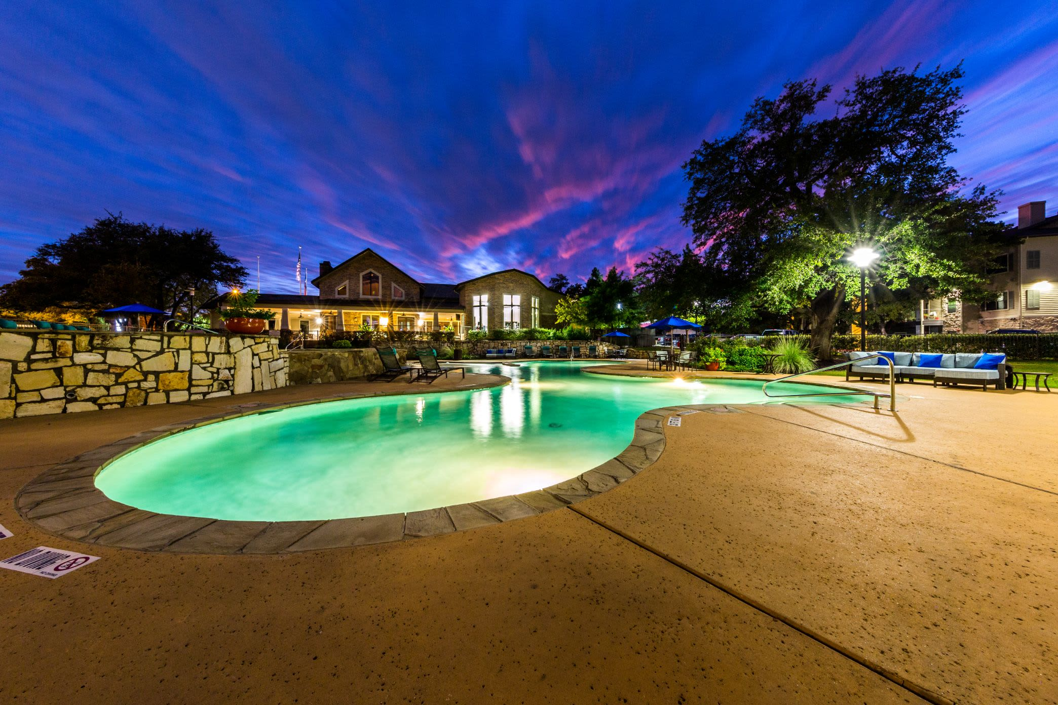 Lit pool beneath purple skies at Marquis on Lakeline in Cedar Park, Texas