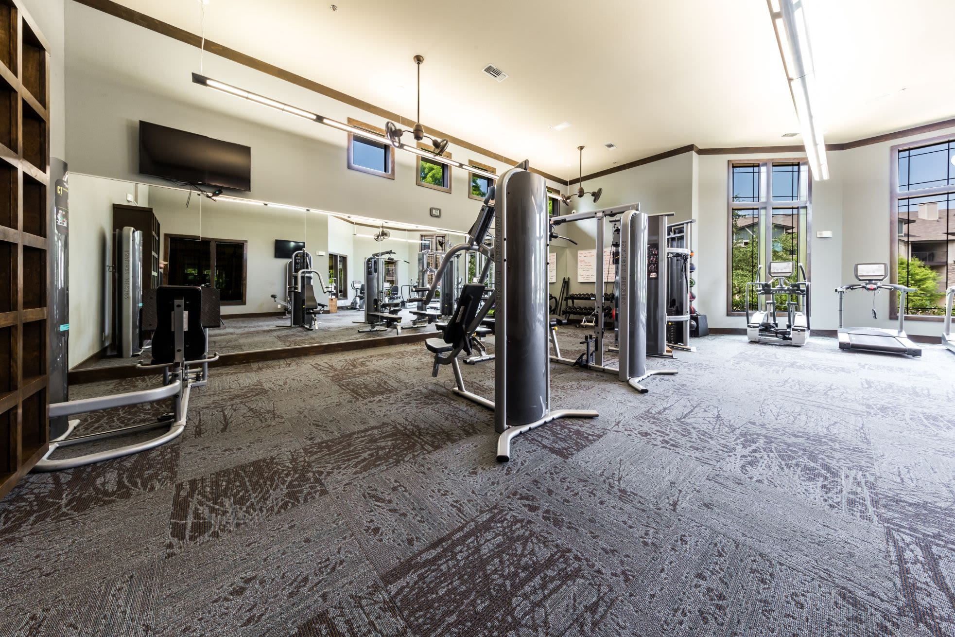 Cable machines and large mirrors in the fitness center at Marquis on Lakeline in Cedar Park, Texas