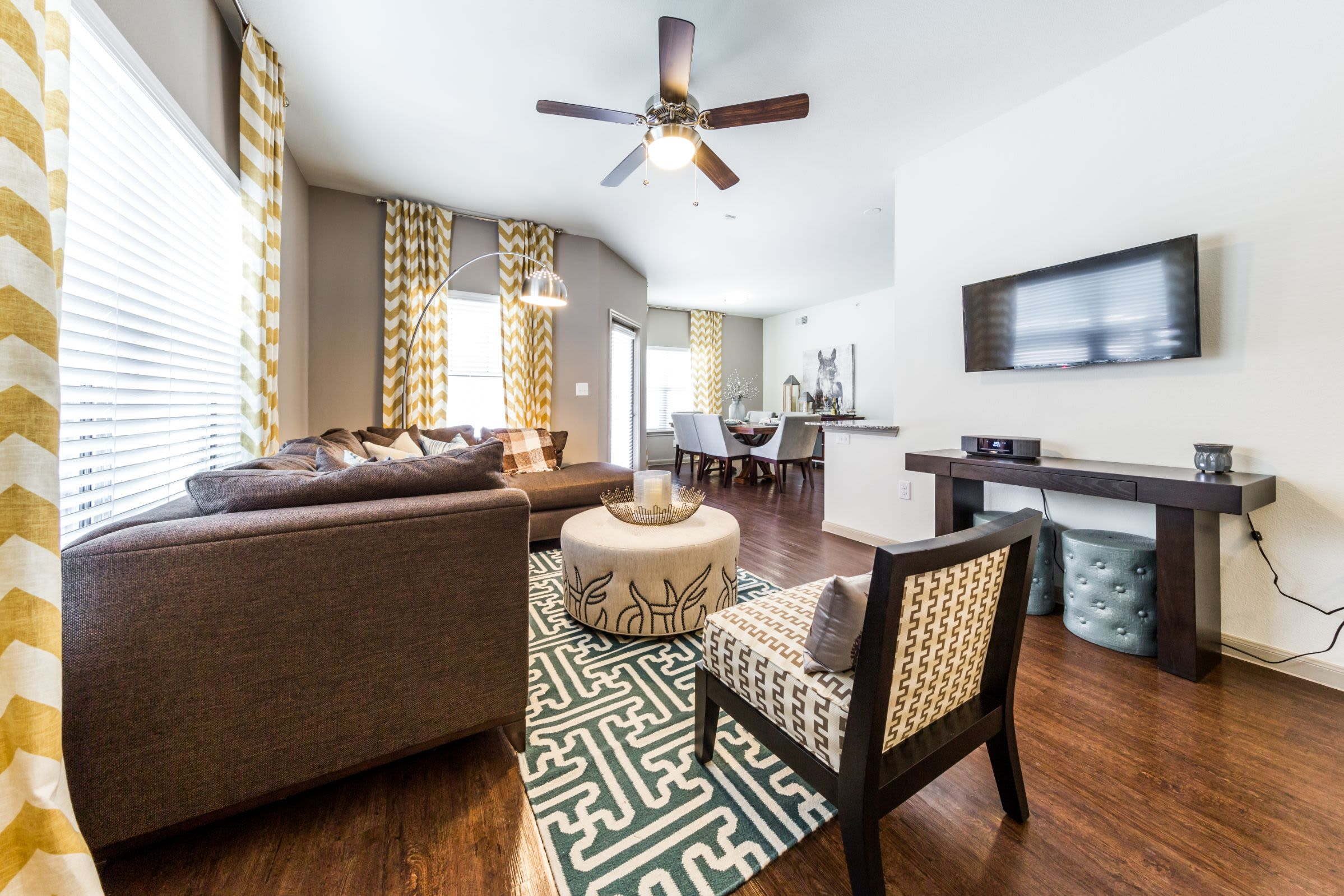 Living area with wood floors and a ceiling fan at Marquis on Lakeline in Cedar Park, Texas