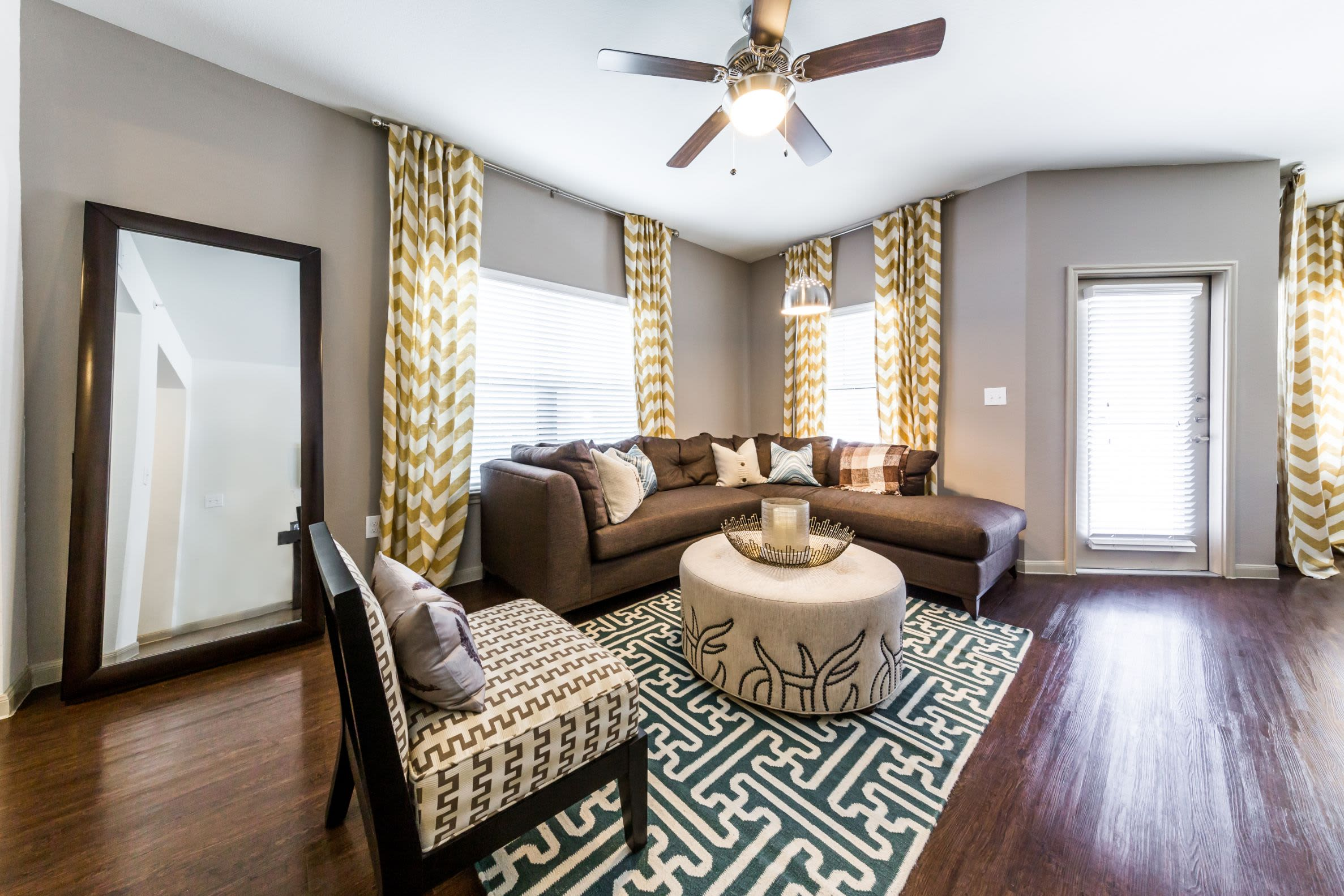 Bright living area with multiple windows and wood flooring at Marquis on Lakeline in Cedar Park, Texas