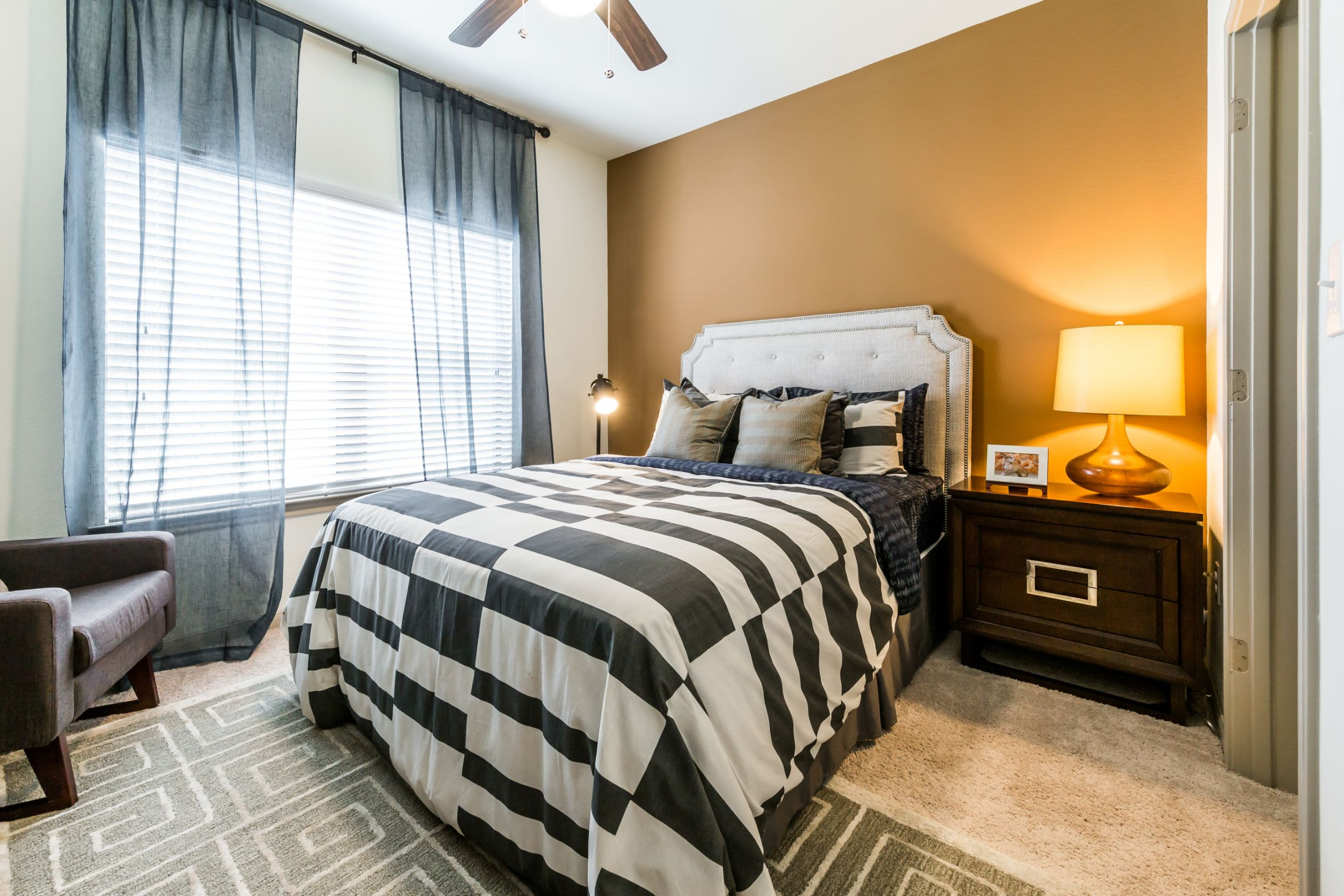 Bedroom with a large window and an accent wall at Marquis on Lakeline in Cedar Park, Texas
