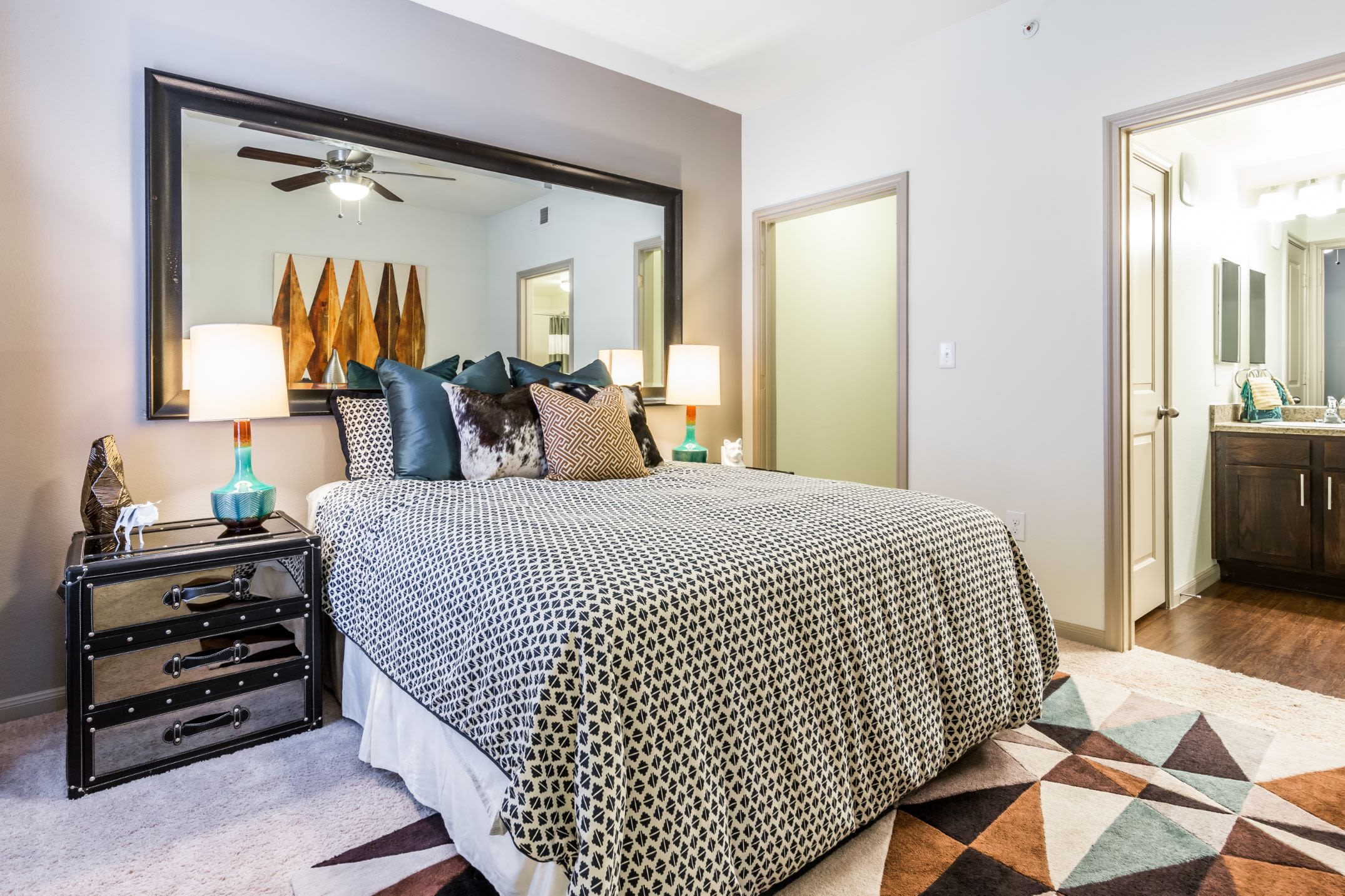 Bright bedroom with a large mirror behind the bed at Marquis on Lakeline in Cedar Park, Texas