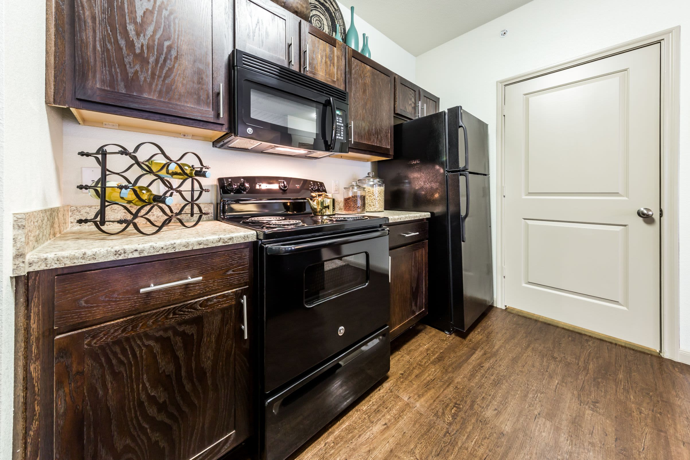 Kitchen with wood floors and black appliances at Marquis on Lakeline in Cedar Park, Texas