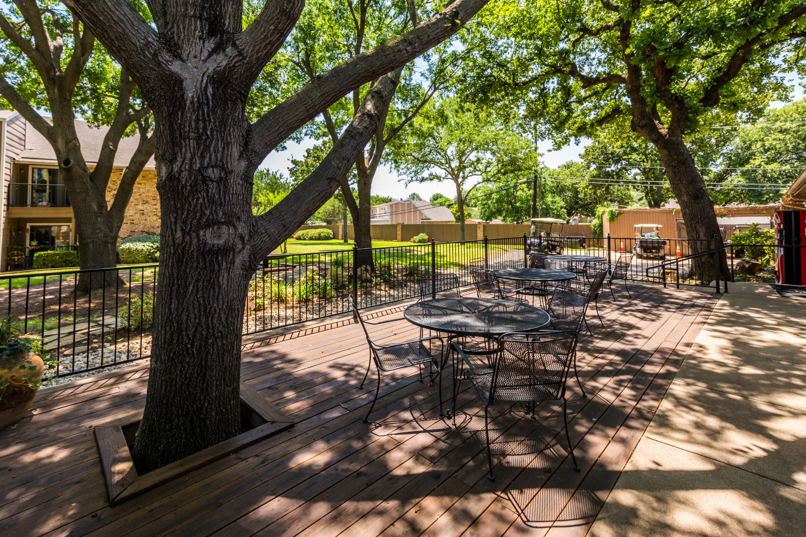 Outdoor seating area shaded by trees at The Park at Flower Mound in Flower Mound, Texas
