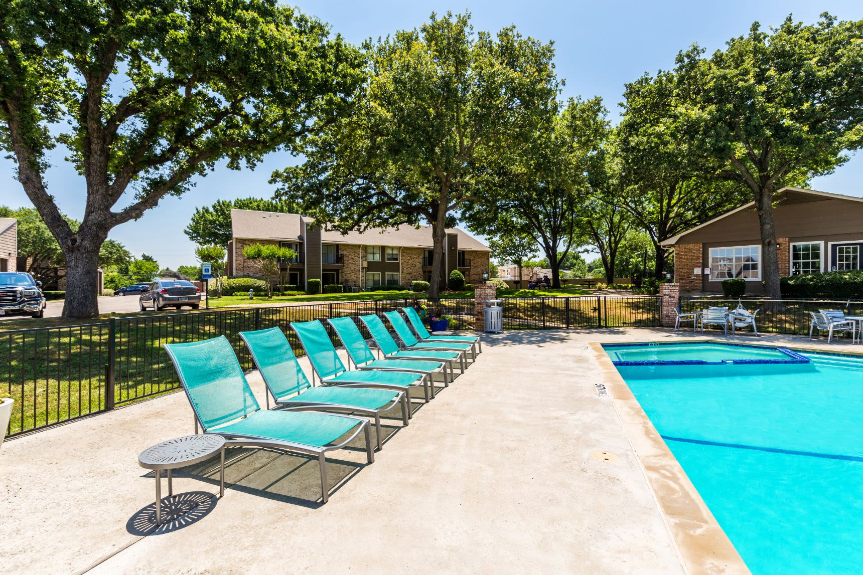 Row of sun chairs next to the pool at The Park at Flower Mound in Flower Mound, Texas