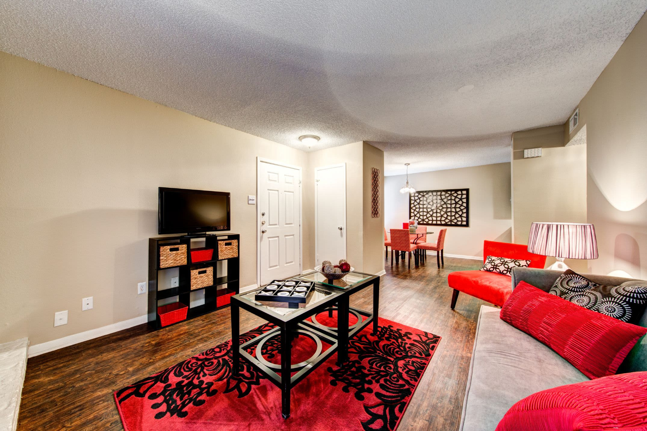 Living room with red accents at The Park at Flower Mound in Flower Mound, Texas