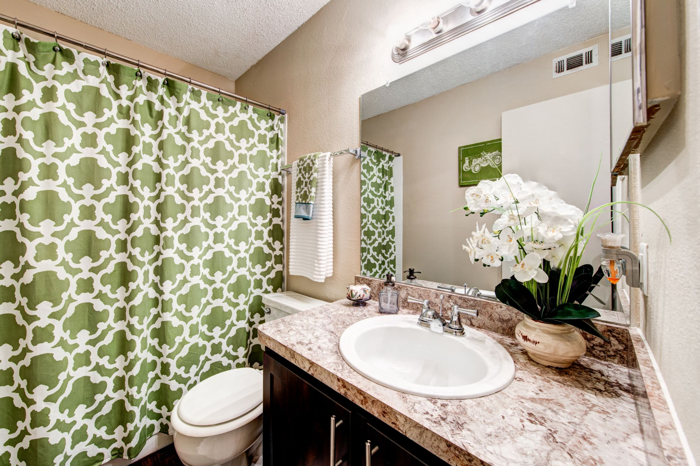 Bathroom with dark colored cabinets at The Park at Flower Mound in Flower Mound, Texas