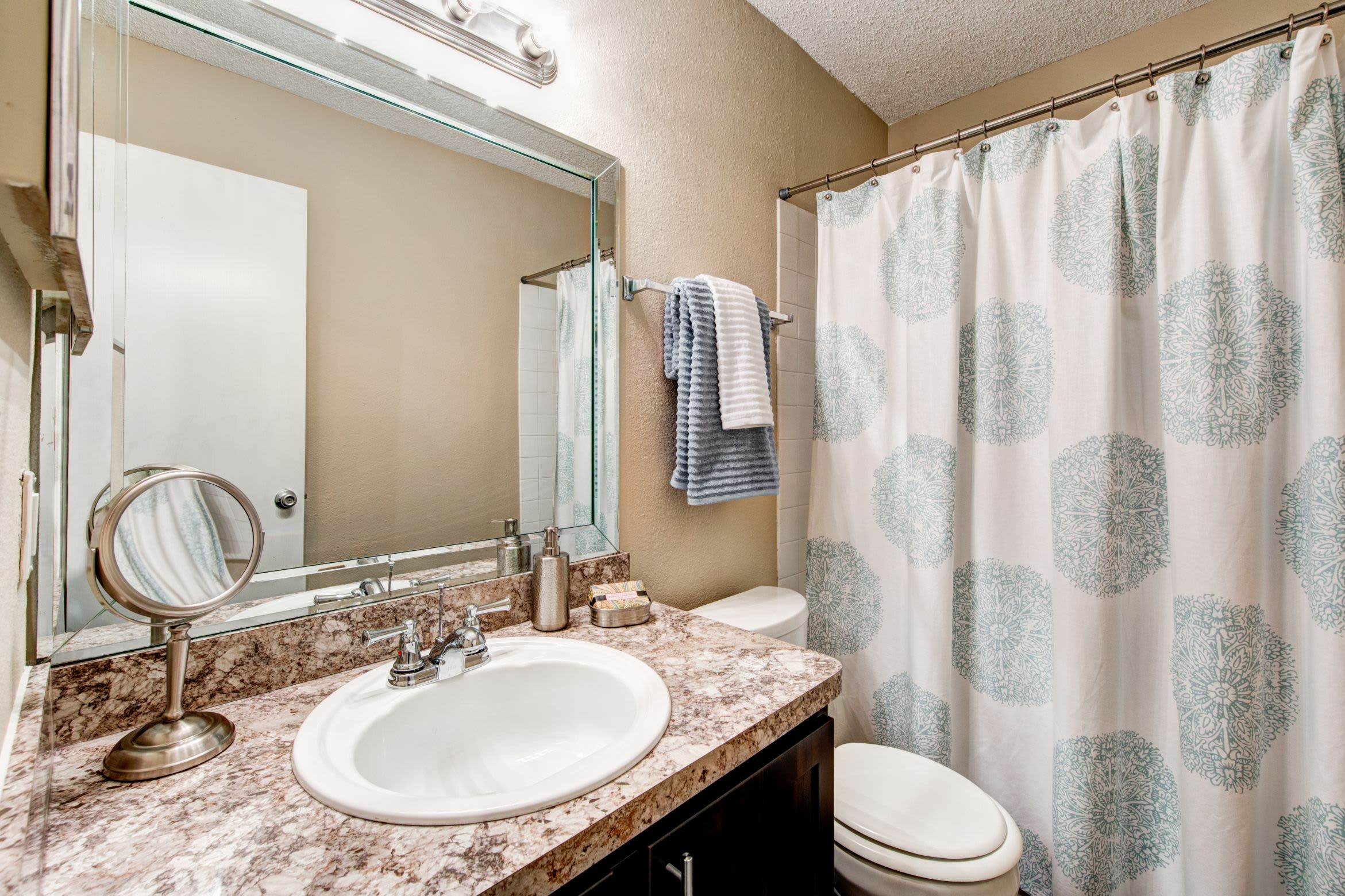 Bathroom with granite style counters at The Park at Flower Mound in Flower Mound, Texas