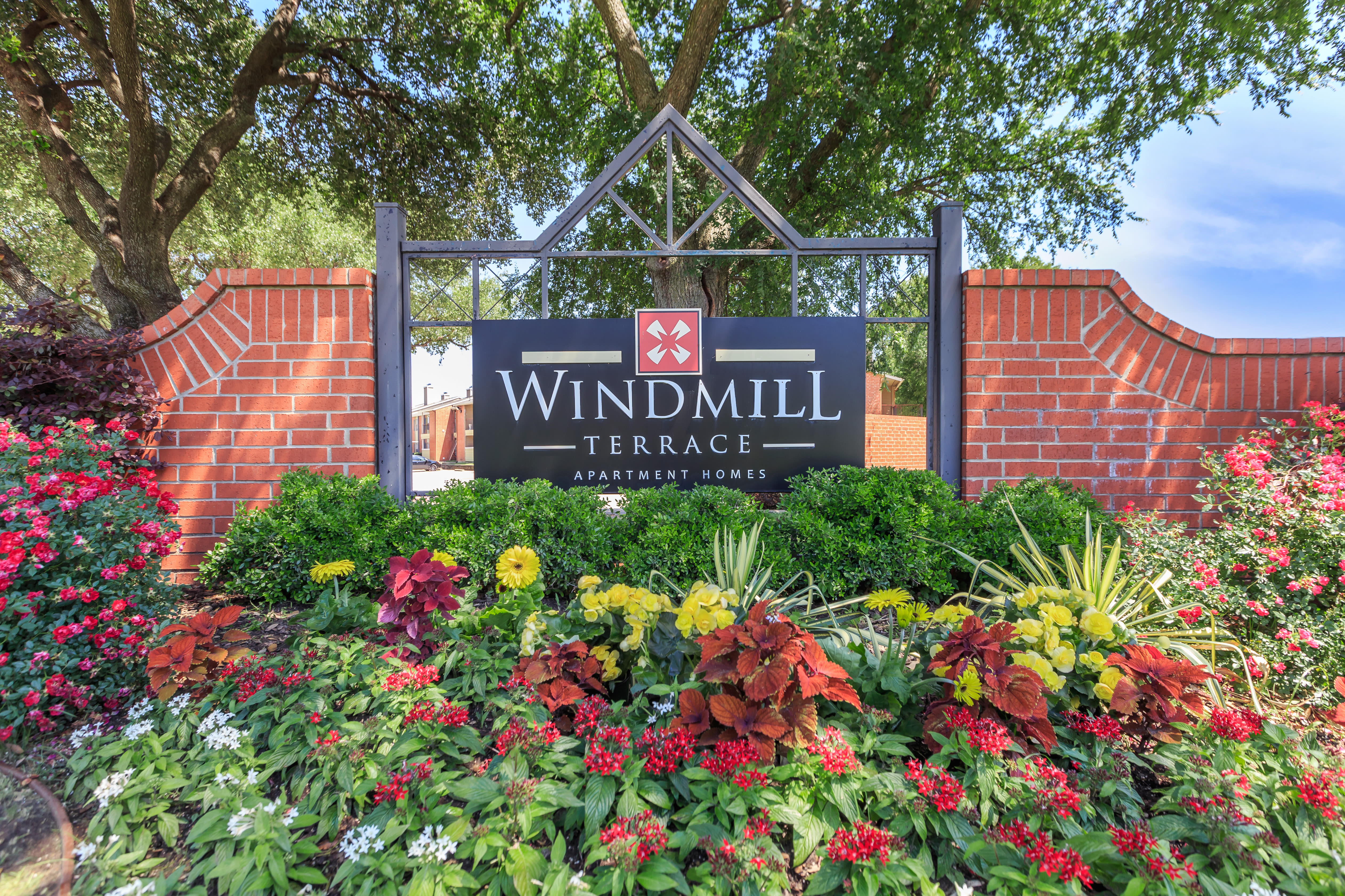 Sign surrounded by flowers at Windmill Terrace in Bedford, Texas